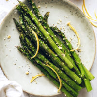 Small plate of roasted asparagus with lemon and vegan parmesan
