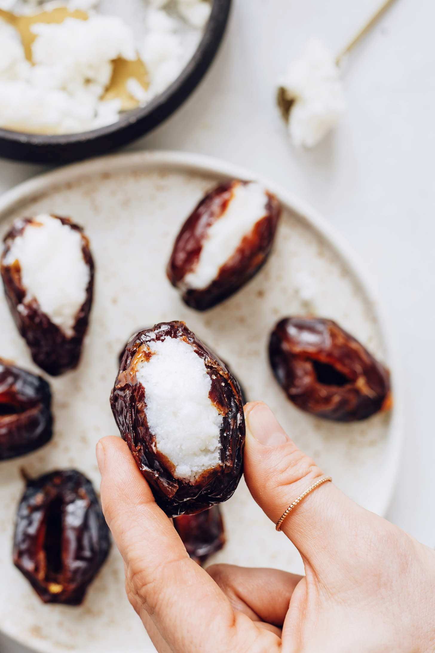 Holding a medjool date stuffed with coconut butter