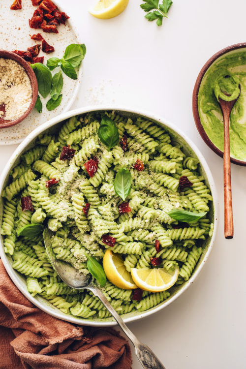 Large plate of creamy avocado pesto pasta salad next to a bowl of avocado pesto
