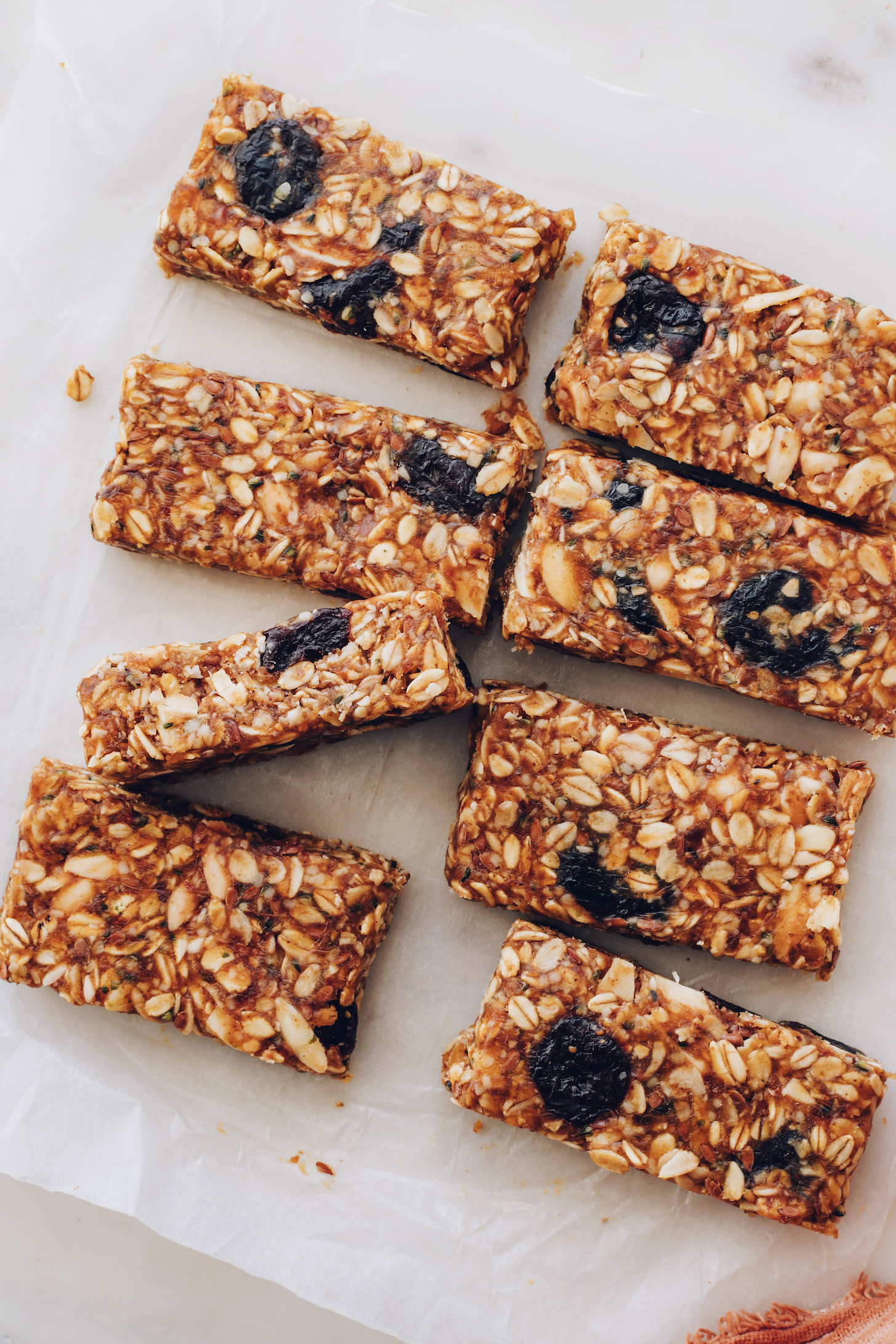 Sliced cherry almond granola bars on a piece of parchment paper