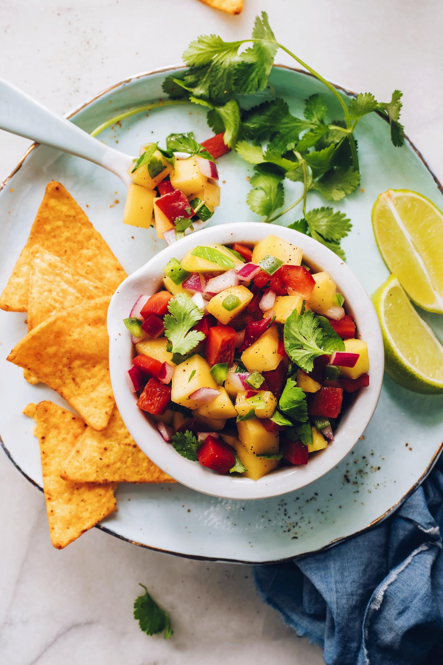 Cucharada y tazón de salsa de mango rodeada de totopos, cilantro y rodajas de lima
