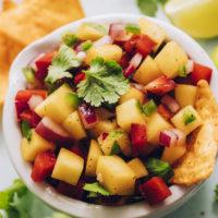 Tortilla chips in a bowl of fresh mango salsa