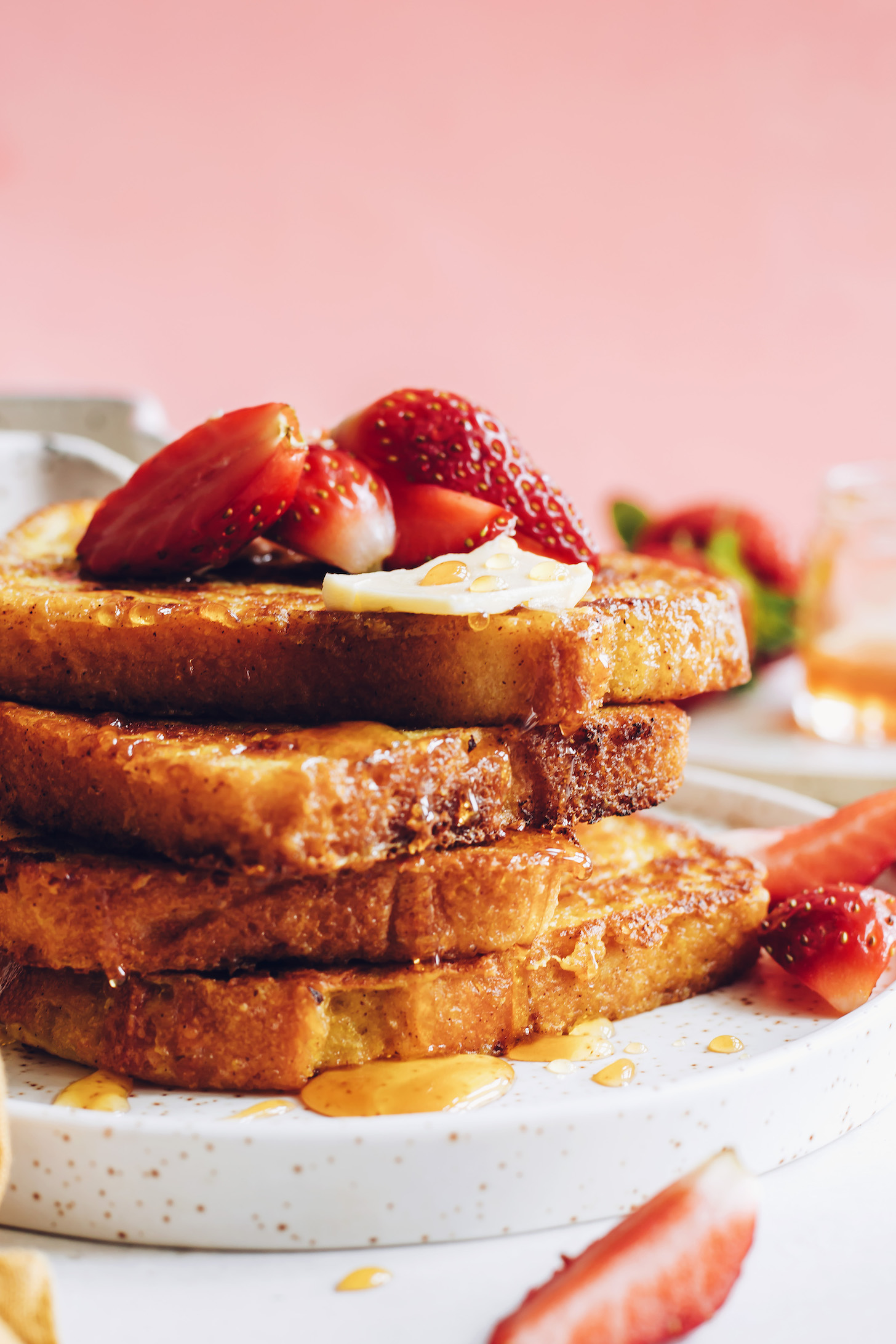 Stack of slices of vegan French toast with vegan butter and strawberries