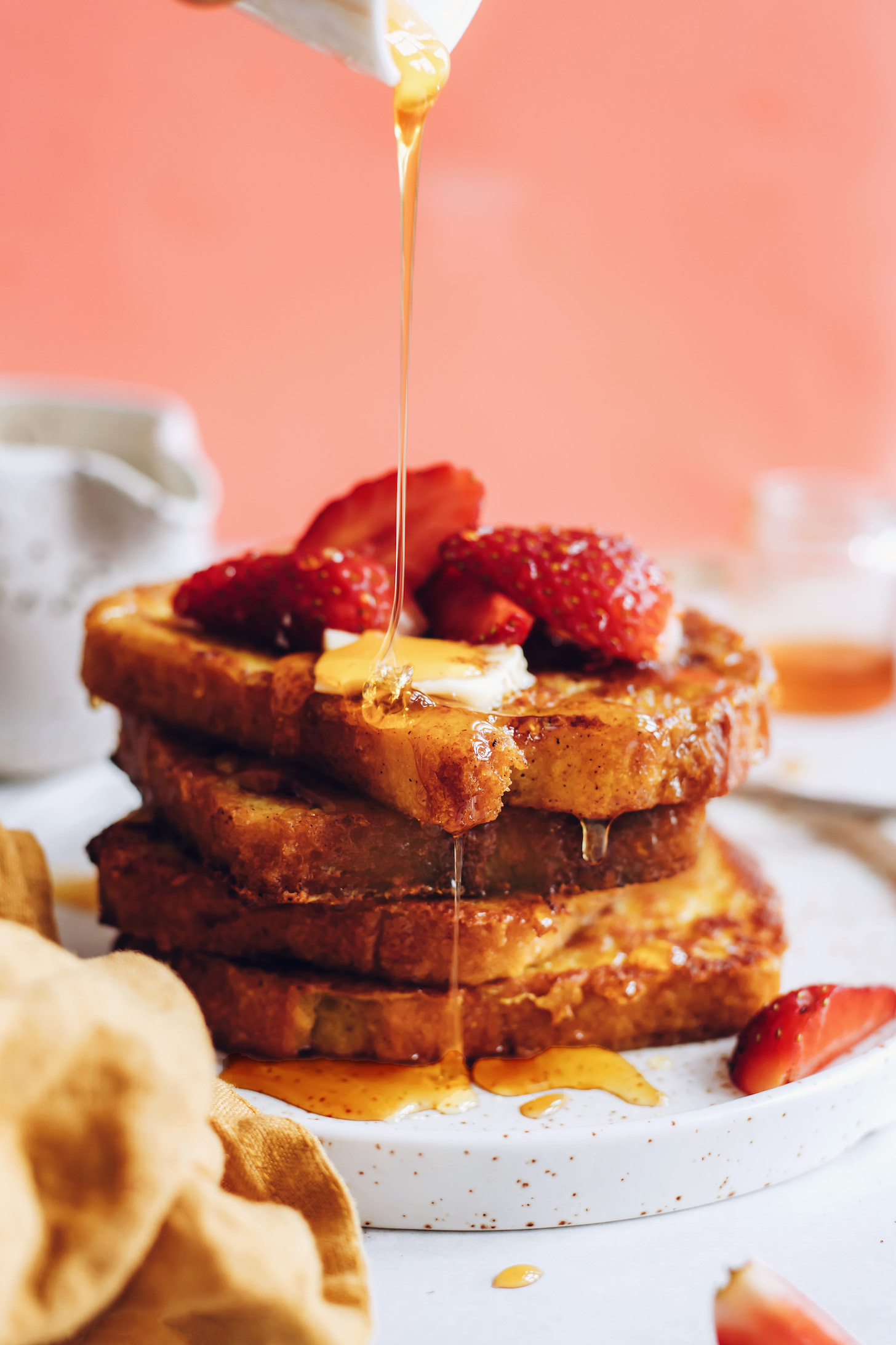 Drizzling slices of vegan French toast with maple syrup