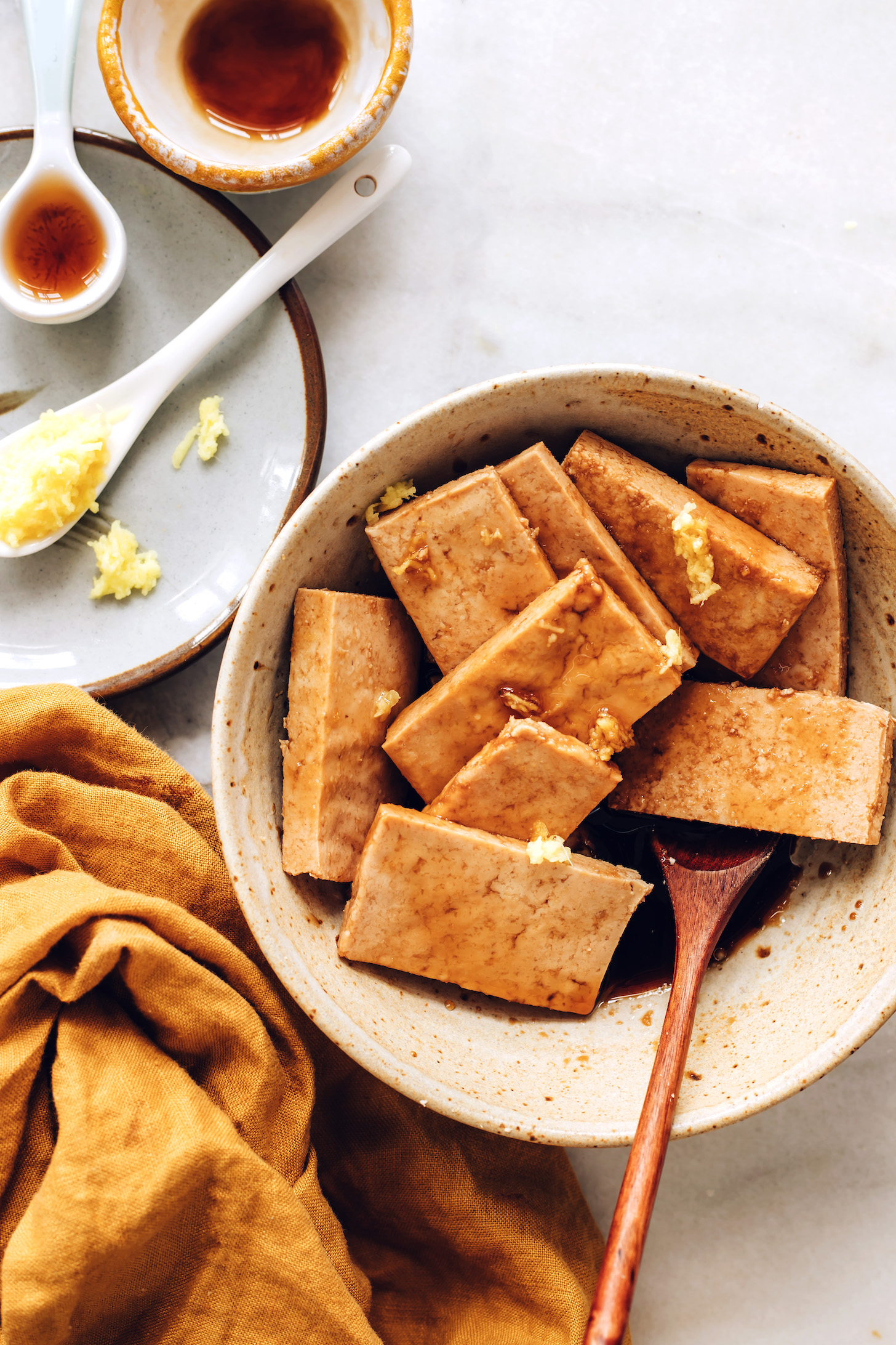 Gingembre, sirop d'érable et huile de sésame à côté d'un bol de tofu mariné au gingembre
