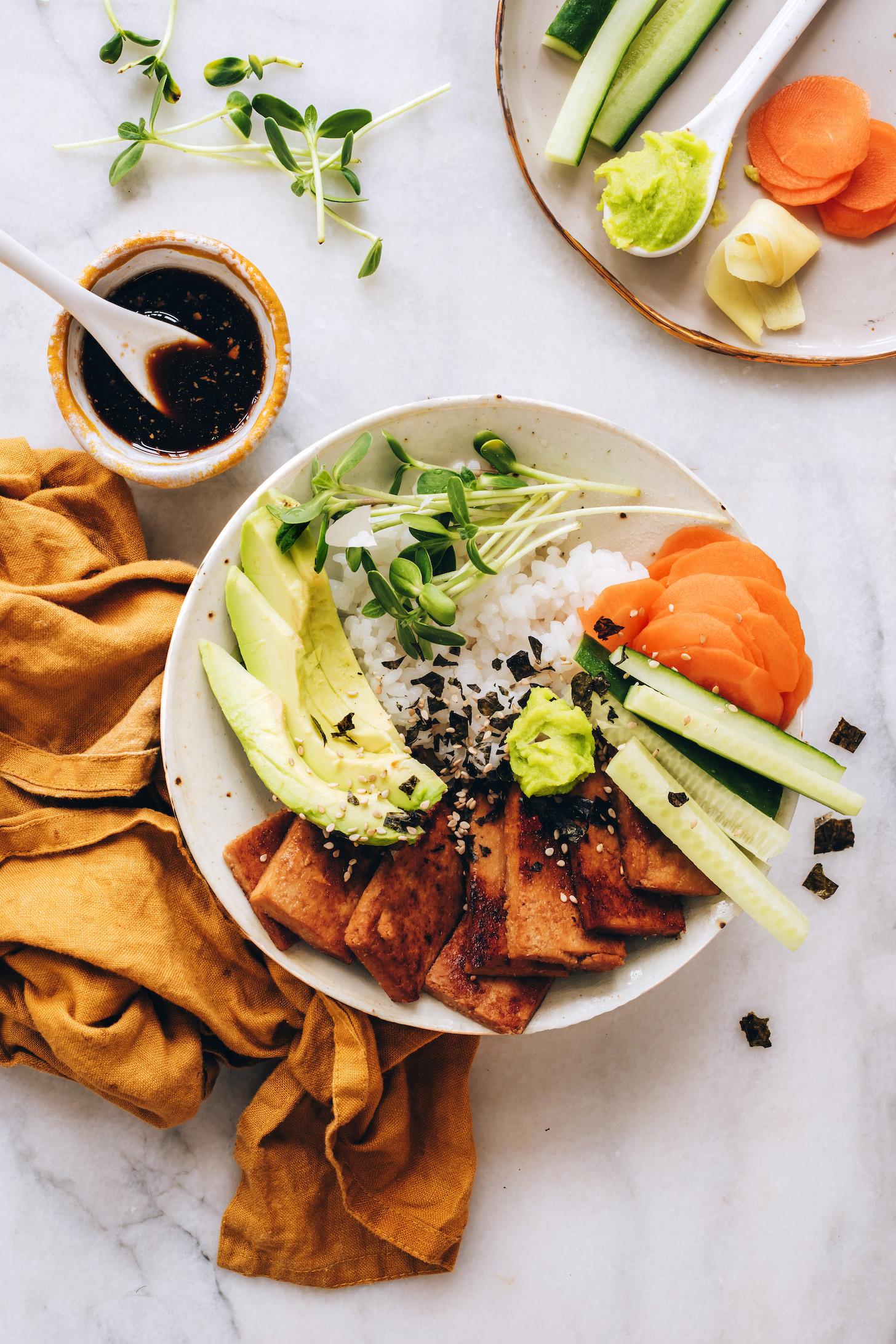 Sauce tamari au gingembre à côté d'un bol de sushi végétalien
