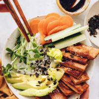 Holding chopsticks over a vegan sushi bowl with ginger marinated tofu