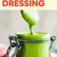 Green goddess dressing sliding off a spoon into a jar