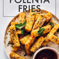 Plate of polenta fries with one dipped in a bowl of marinara