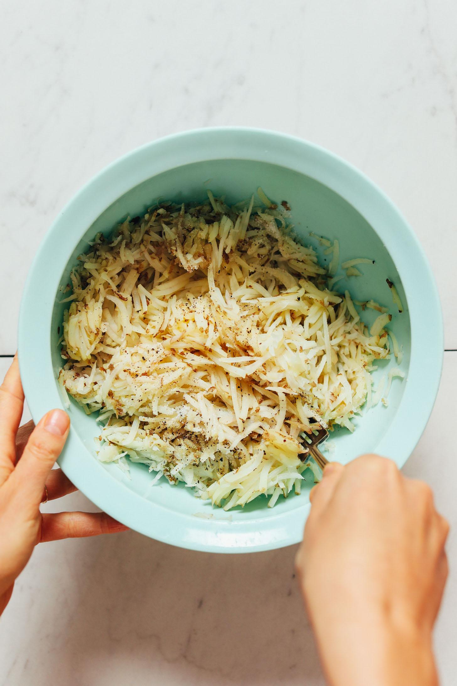 En remuant les pommes de terre râpées avec du sel et du poivre