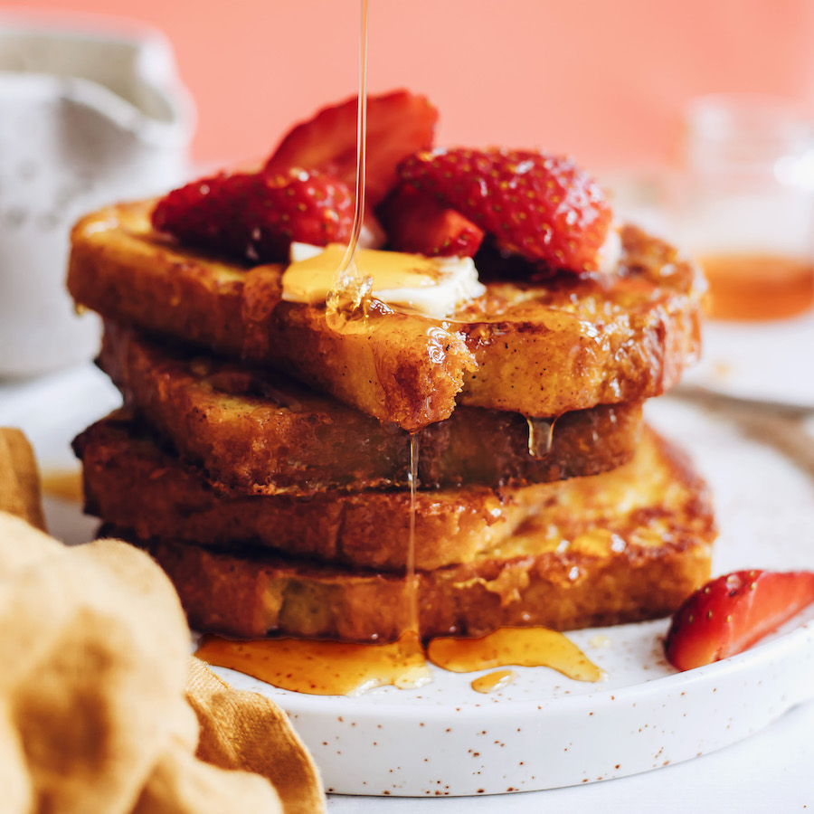 Drizzling maple syrup on slices of vegan French toast with strawberries