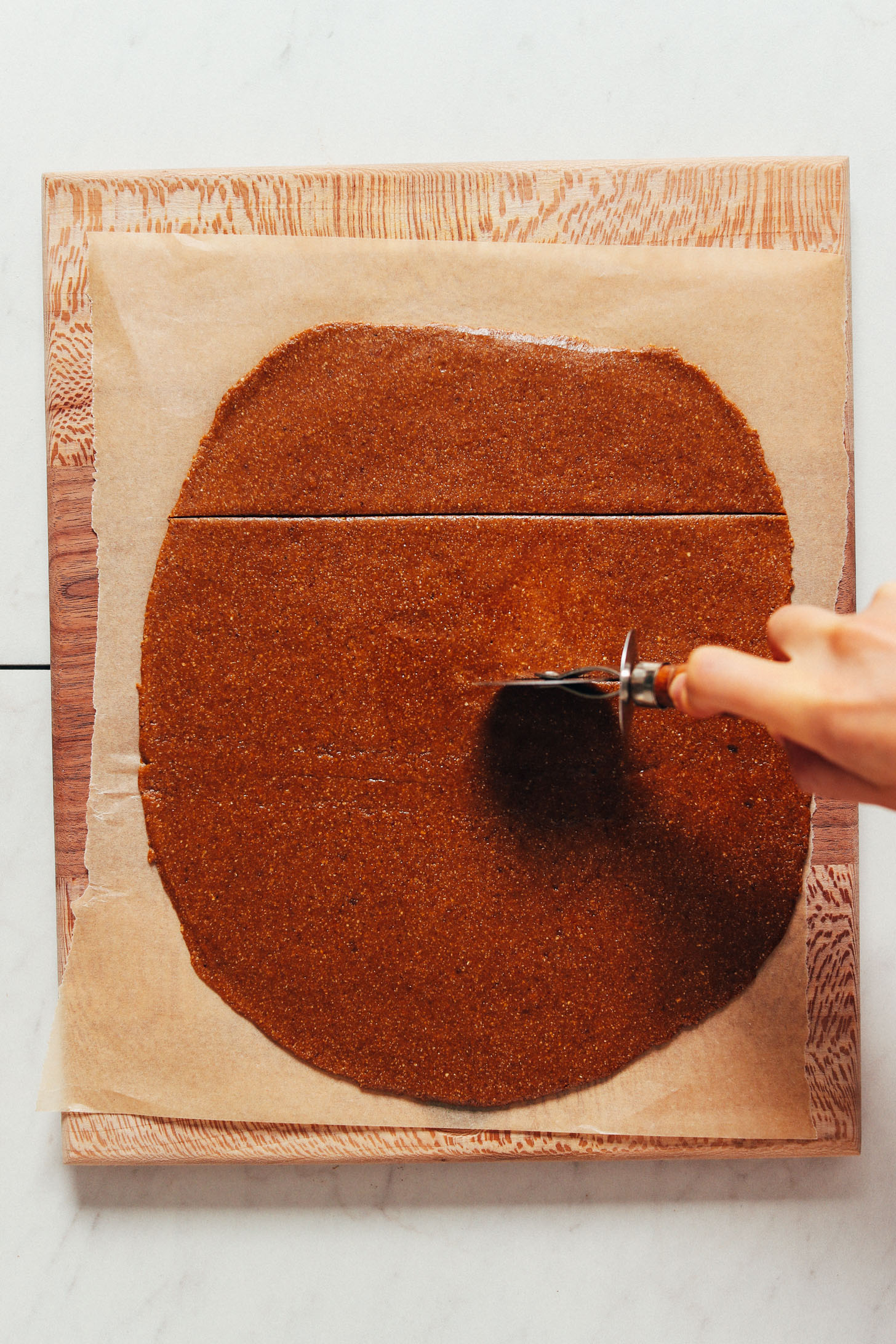 À l'aide d'un coupe-pizza pour couper la pâte en formes de biscuits Graham