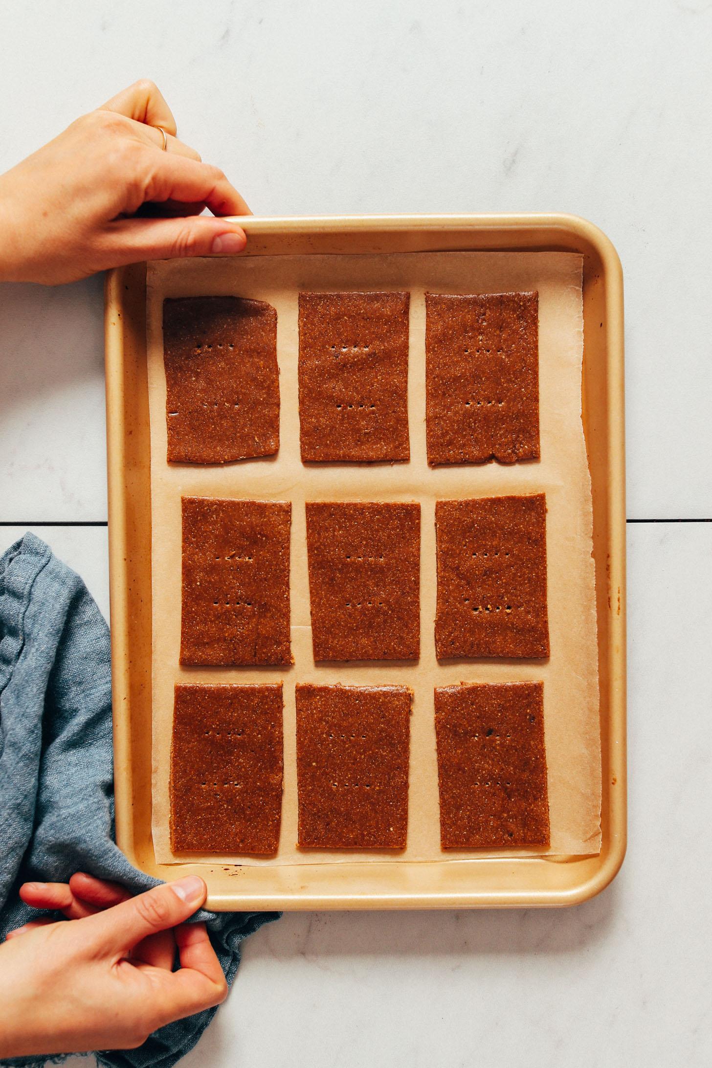 Pâte de biscuits Graham sans gluten sur une plaque à pâtisserie tapissée de papier sulfurisé