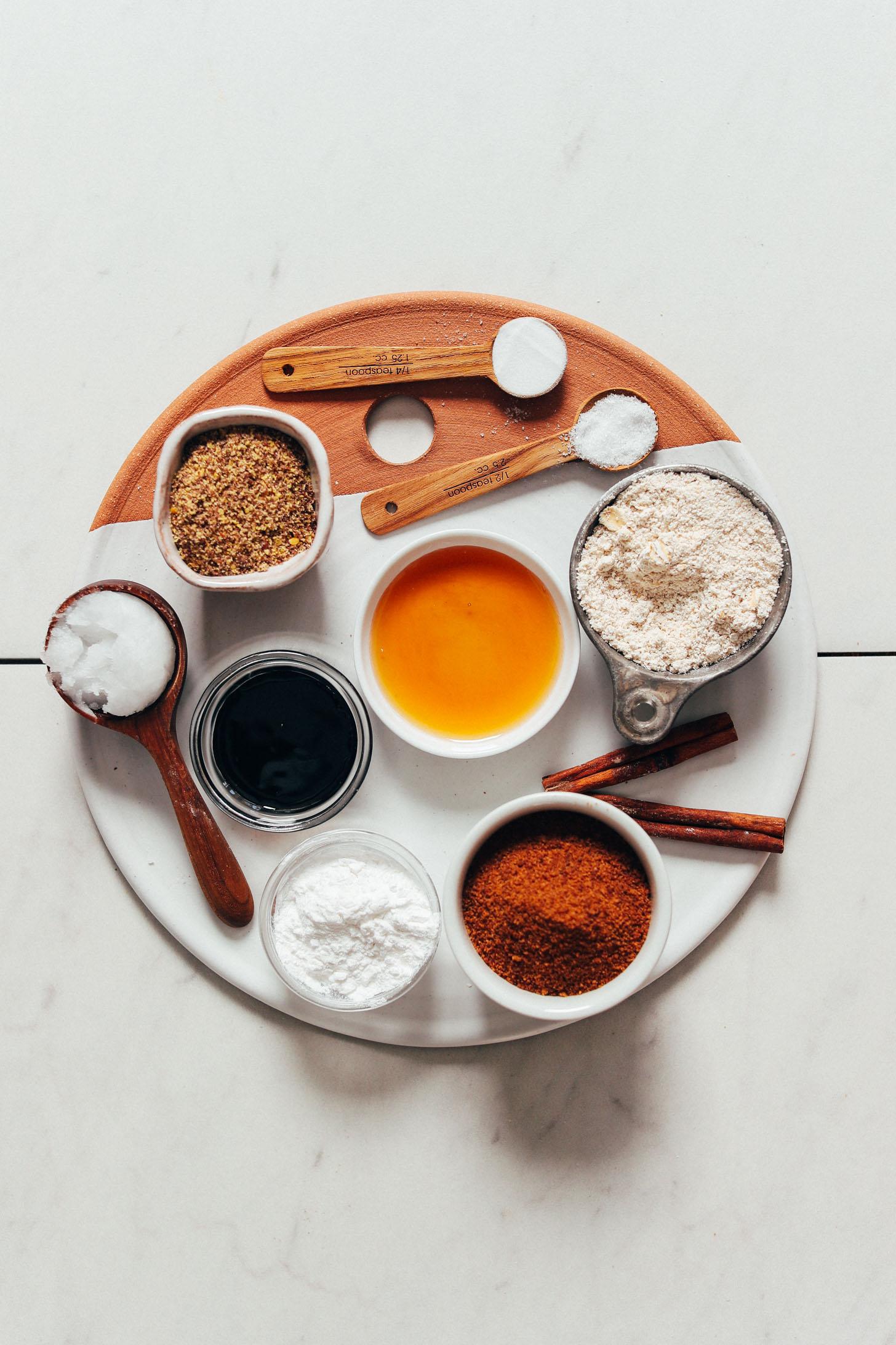 Plateau avec sucre de coco, bicarbonate de soude, sel de mer, cannelle, sirop d'érable, mélasse, huile de coco, farine d'avoine, amidon d'arrow-root et lin moulu