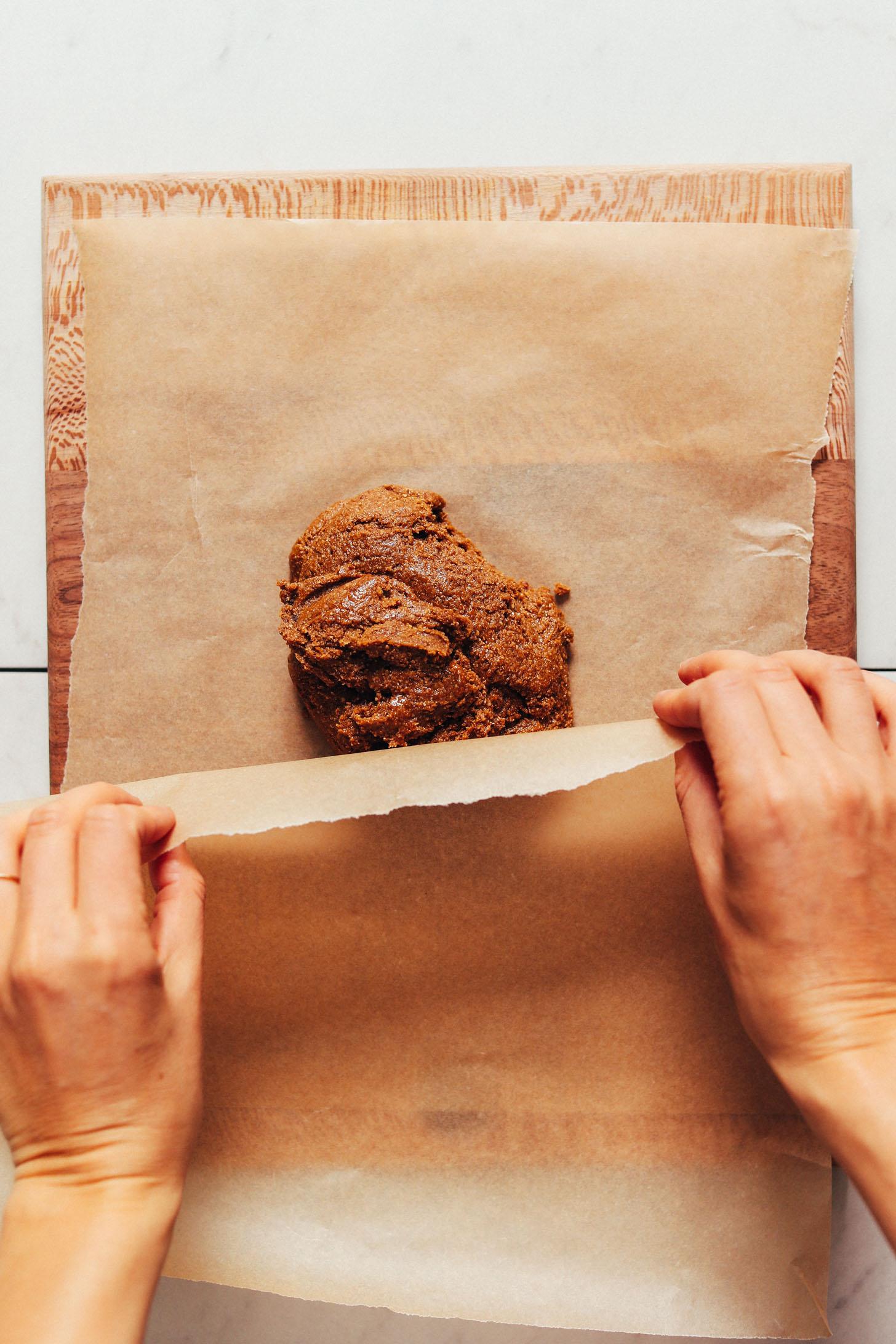 Placer du papier sulfurisé sur une boule de pâte de biscuits Graham sans gluten pour la rouler à plat