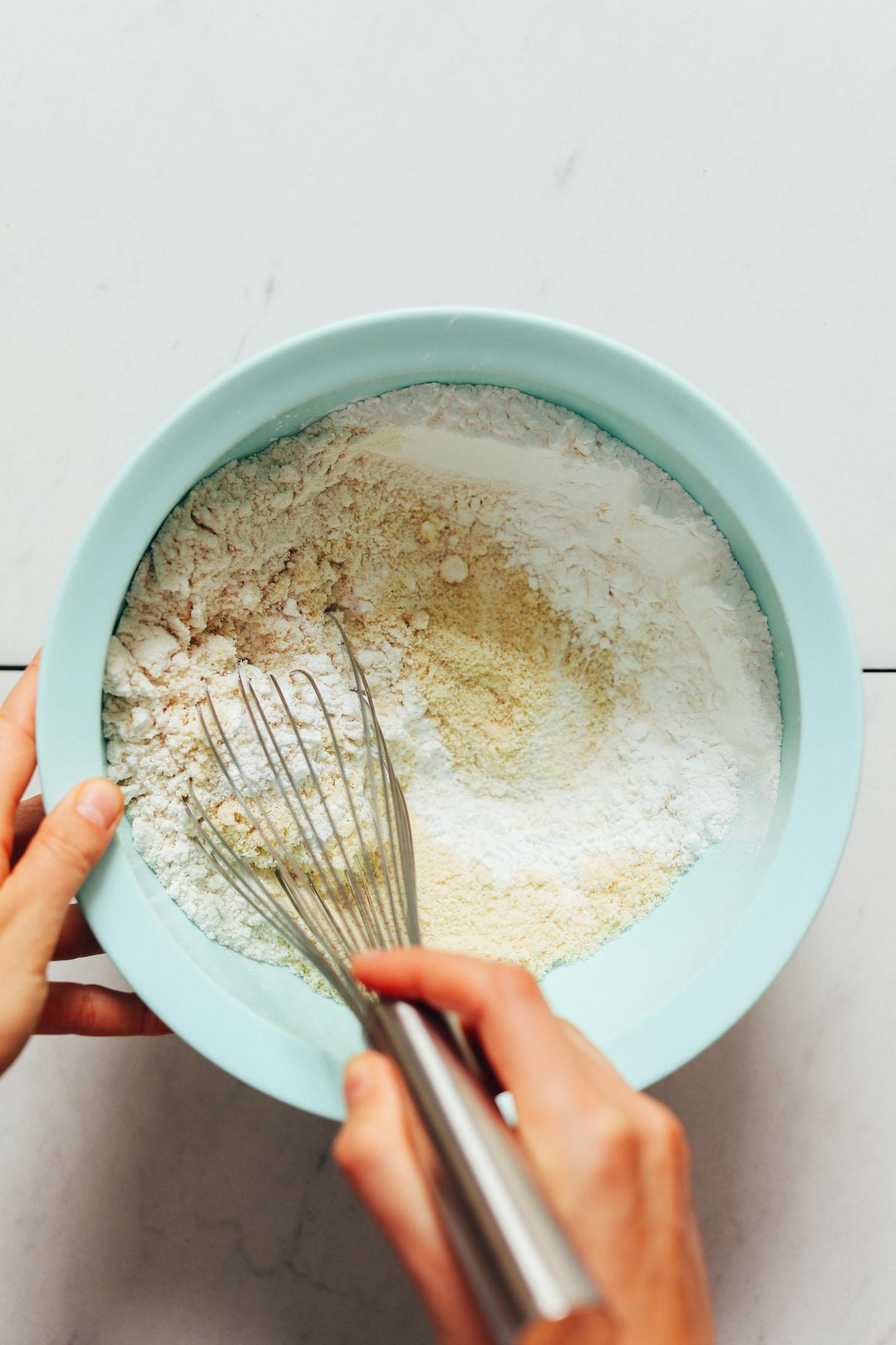 Whisking almond flour, gluten-free flour blend, tapioca flour, baking soda, and sea salt in a bowl