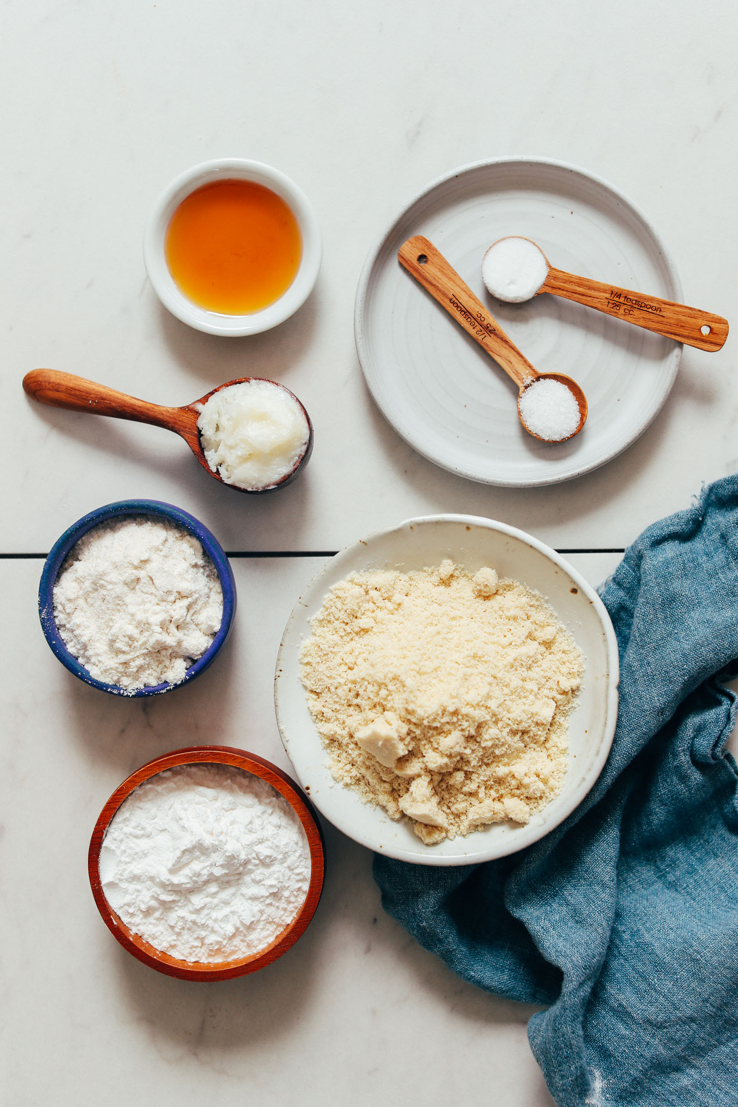 Bowls and spoonfuls of almond flour, gluten-free flour blend, tapioca flour, baking soda, sea salt, coconut oil, and maple syrup