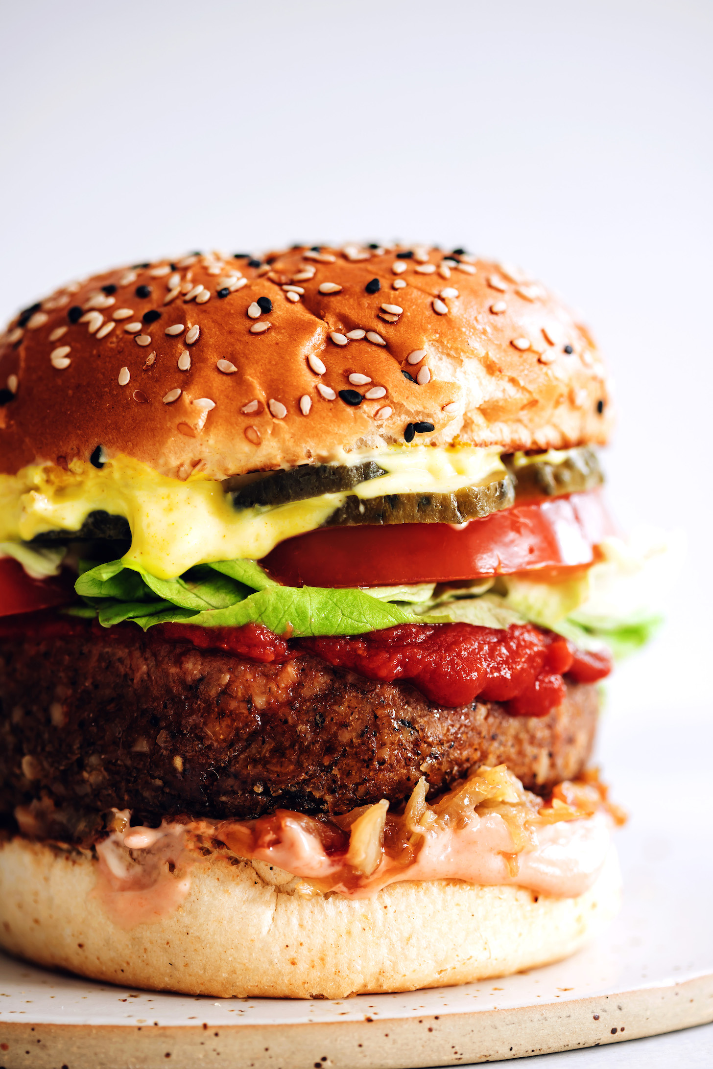 Close up shot of a bun with pickles, mustard, tomato, lettuce, ketchup, vegan burger patty, caramelized onions, and sriracha mayo