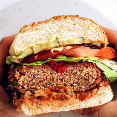 Holding our vegan burger in a bun with lettuce, tomato, and more