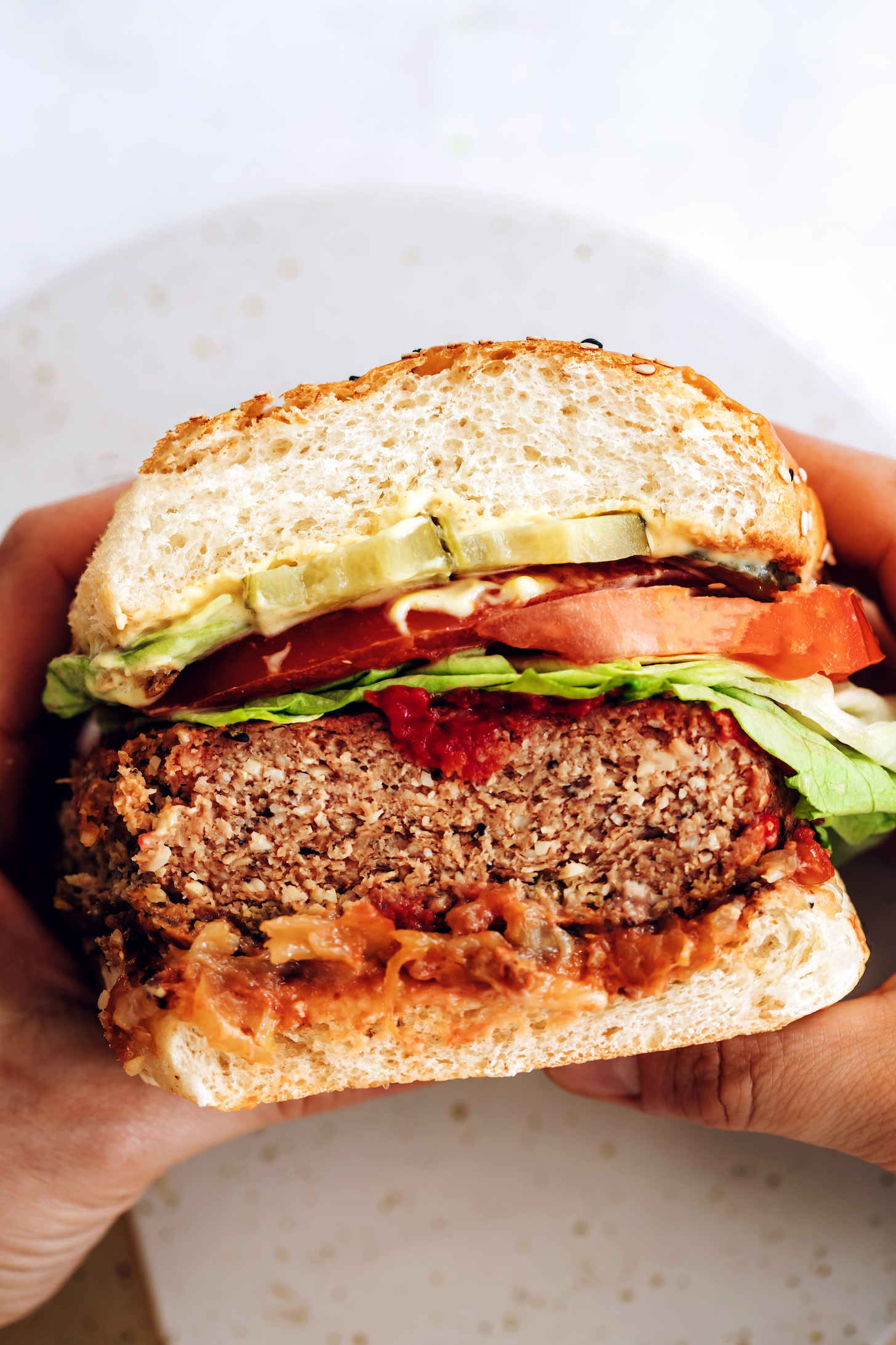 Holding a vegan burger patty in a bun with other toppings