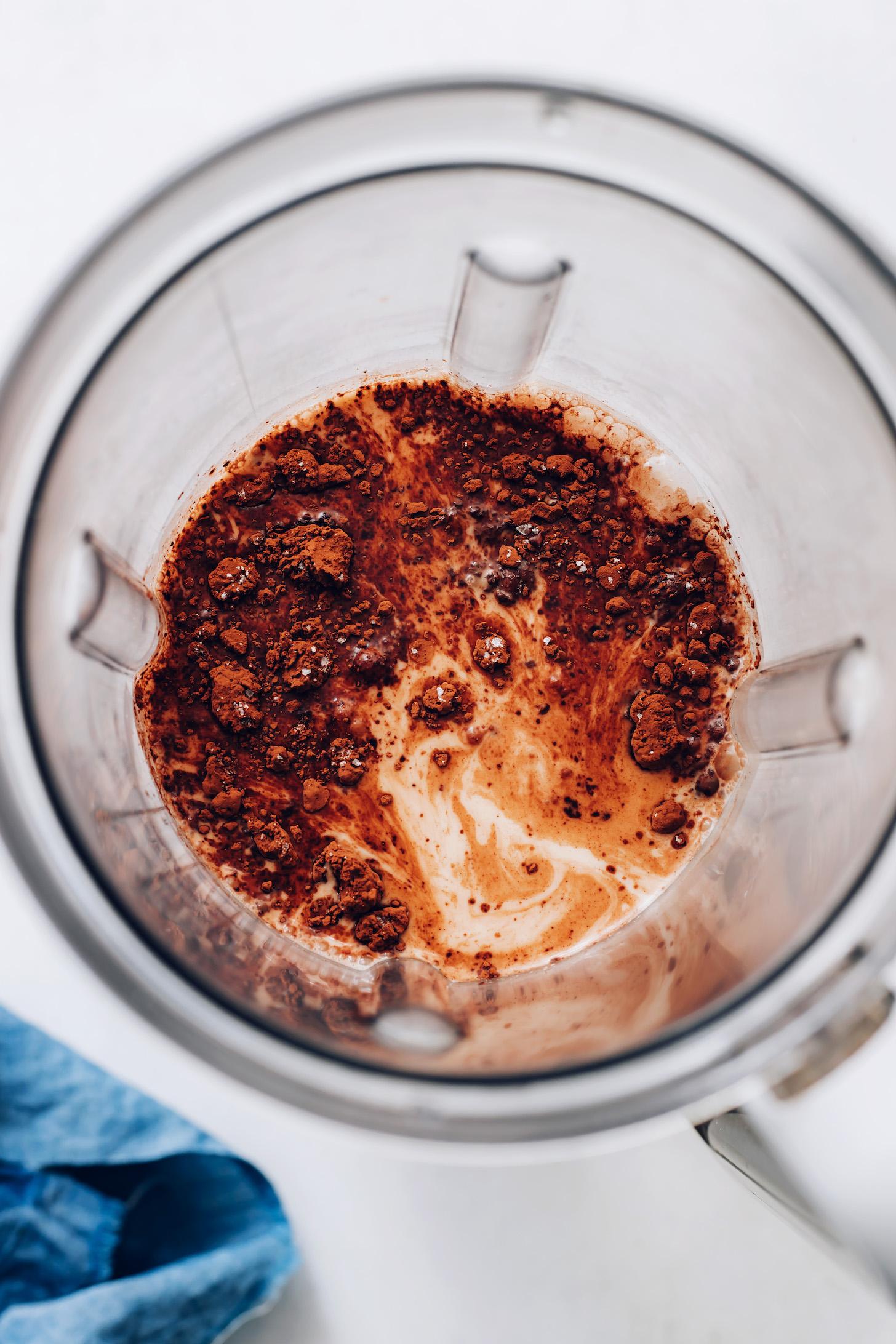 Blender with cocoa powder over creamy hazelnut milk