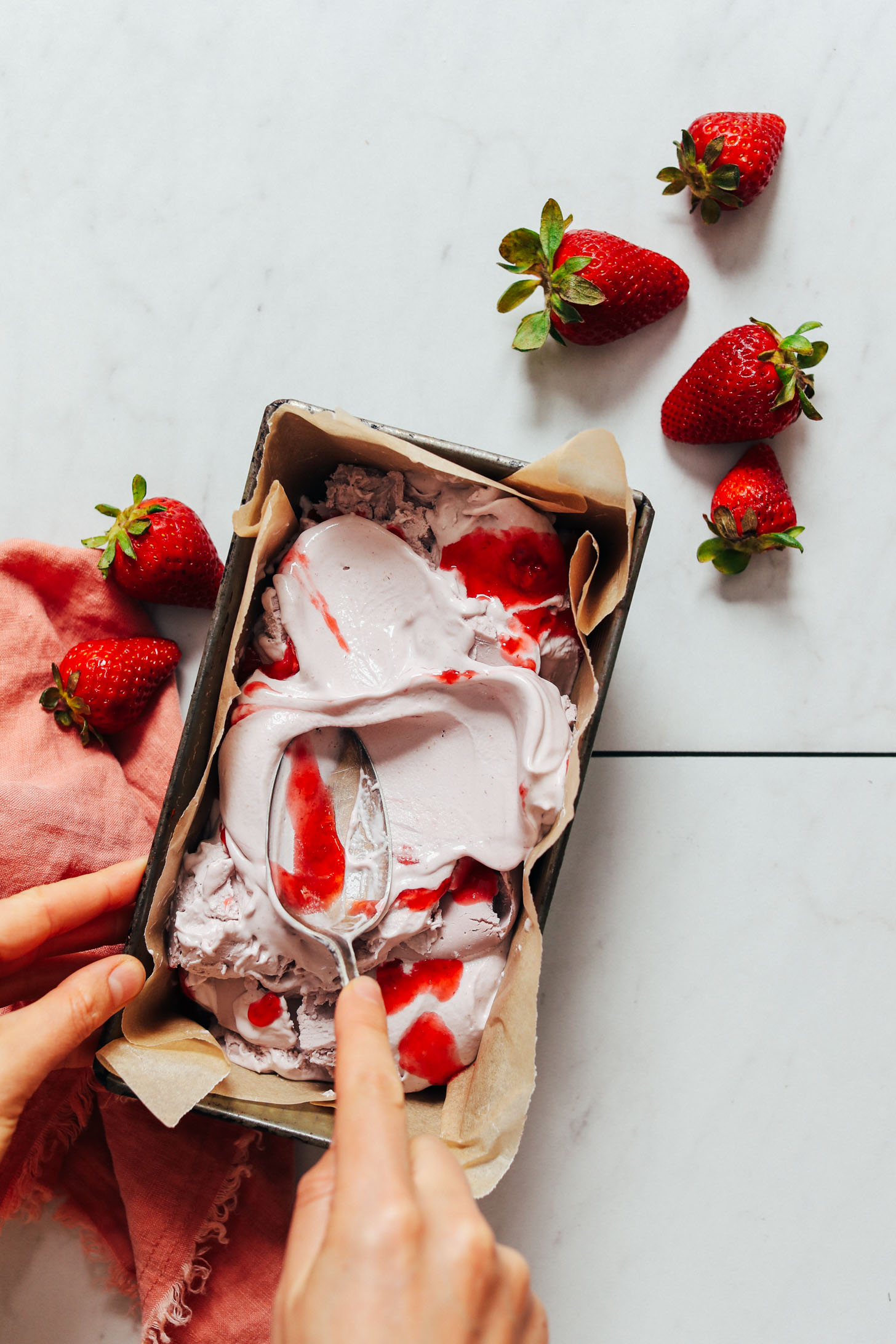 Ajout de tourbillons de compote de fraises à une casserole de glace à la fraise végétalienne