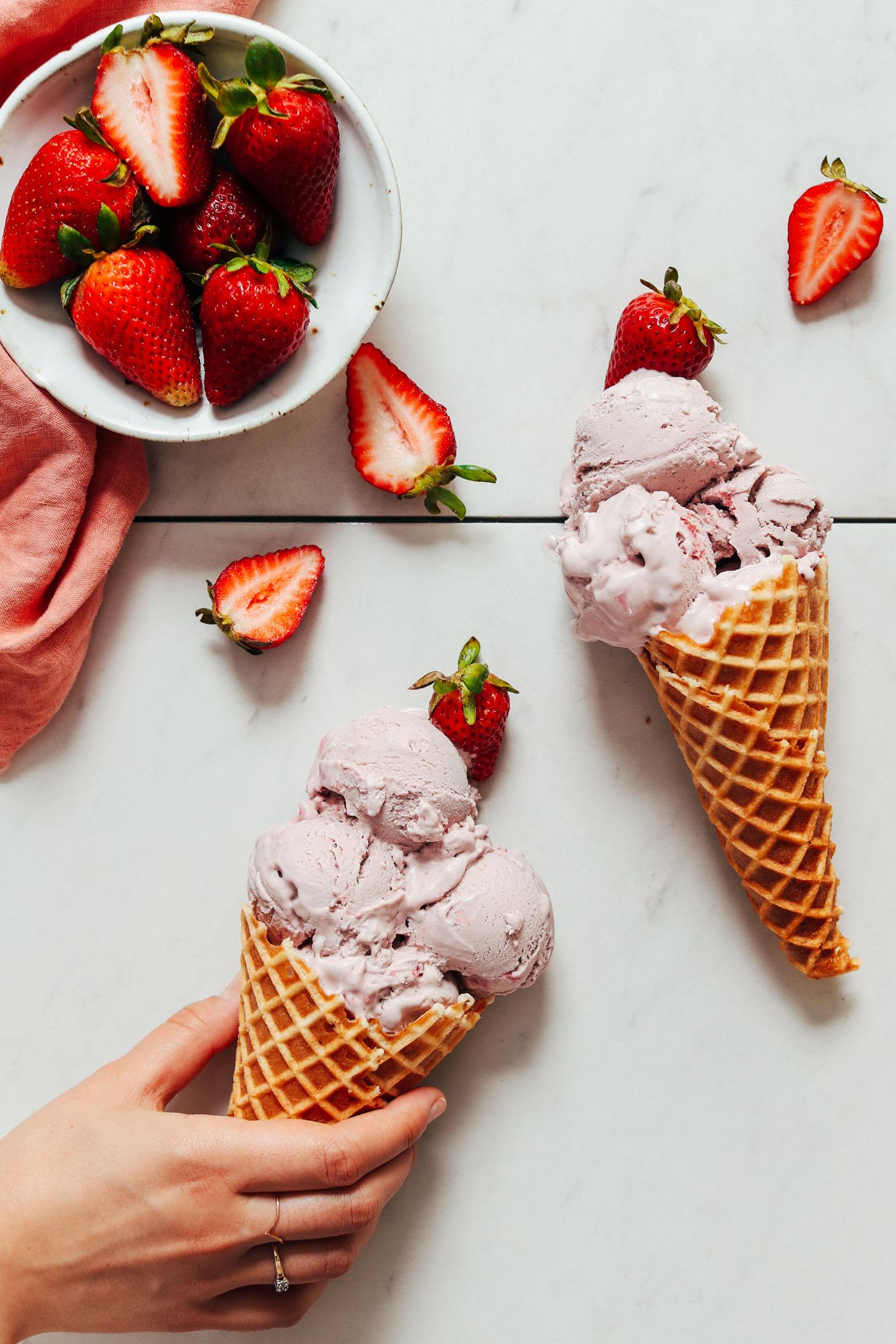 Tenant un cornet gaufré de glace à la fraise végétalienne