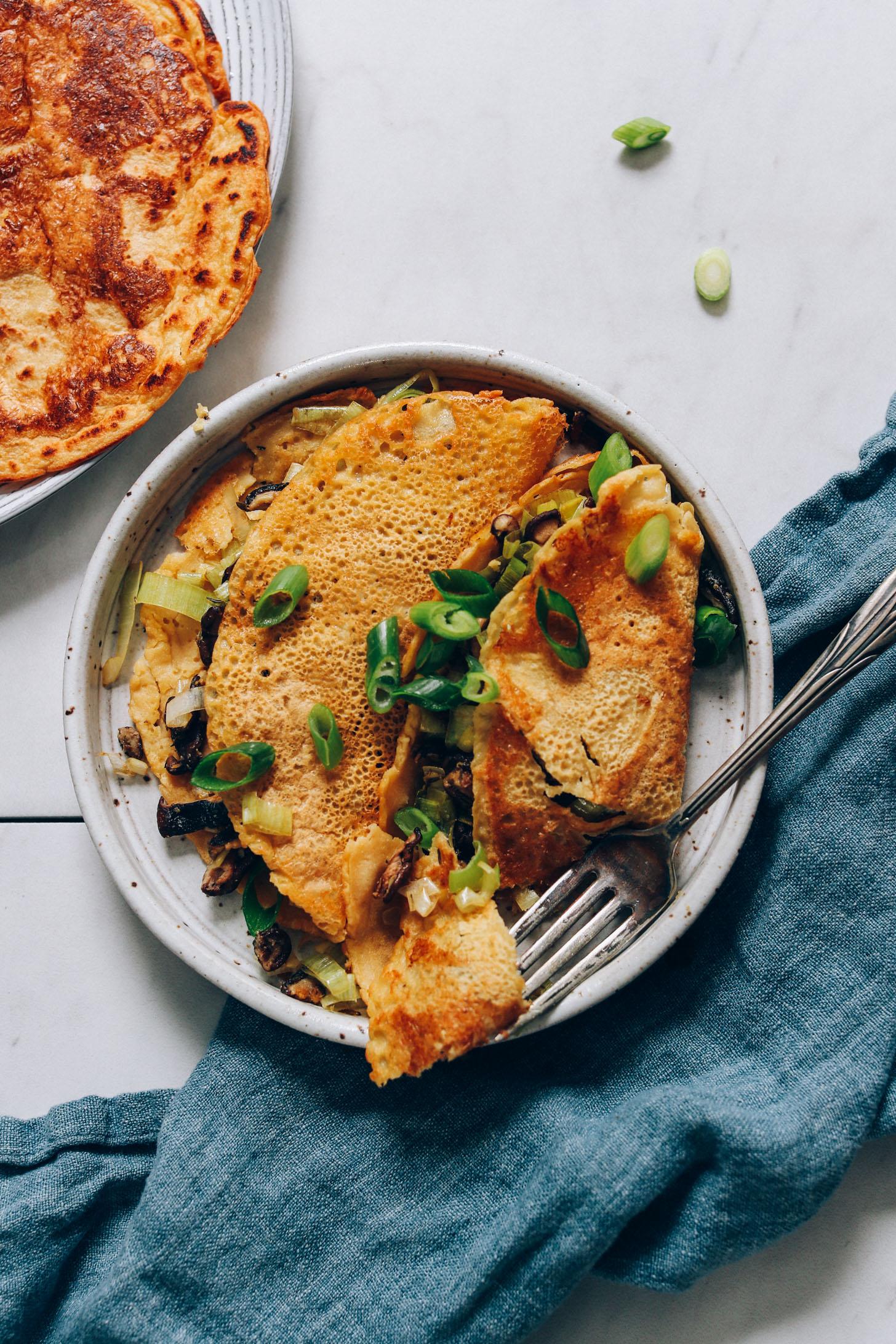 Fourchette posée sur une assiette de crêpes salées aux pois chiches