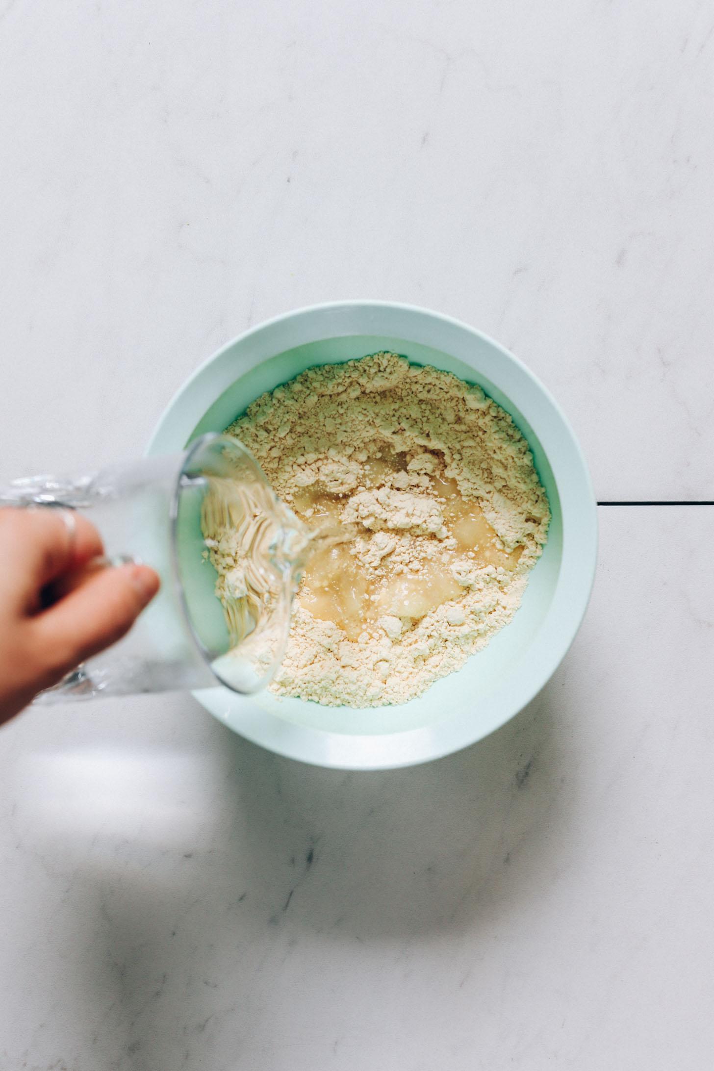 Verser de l'eau dans un bol de farine de pois chiche et de sel