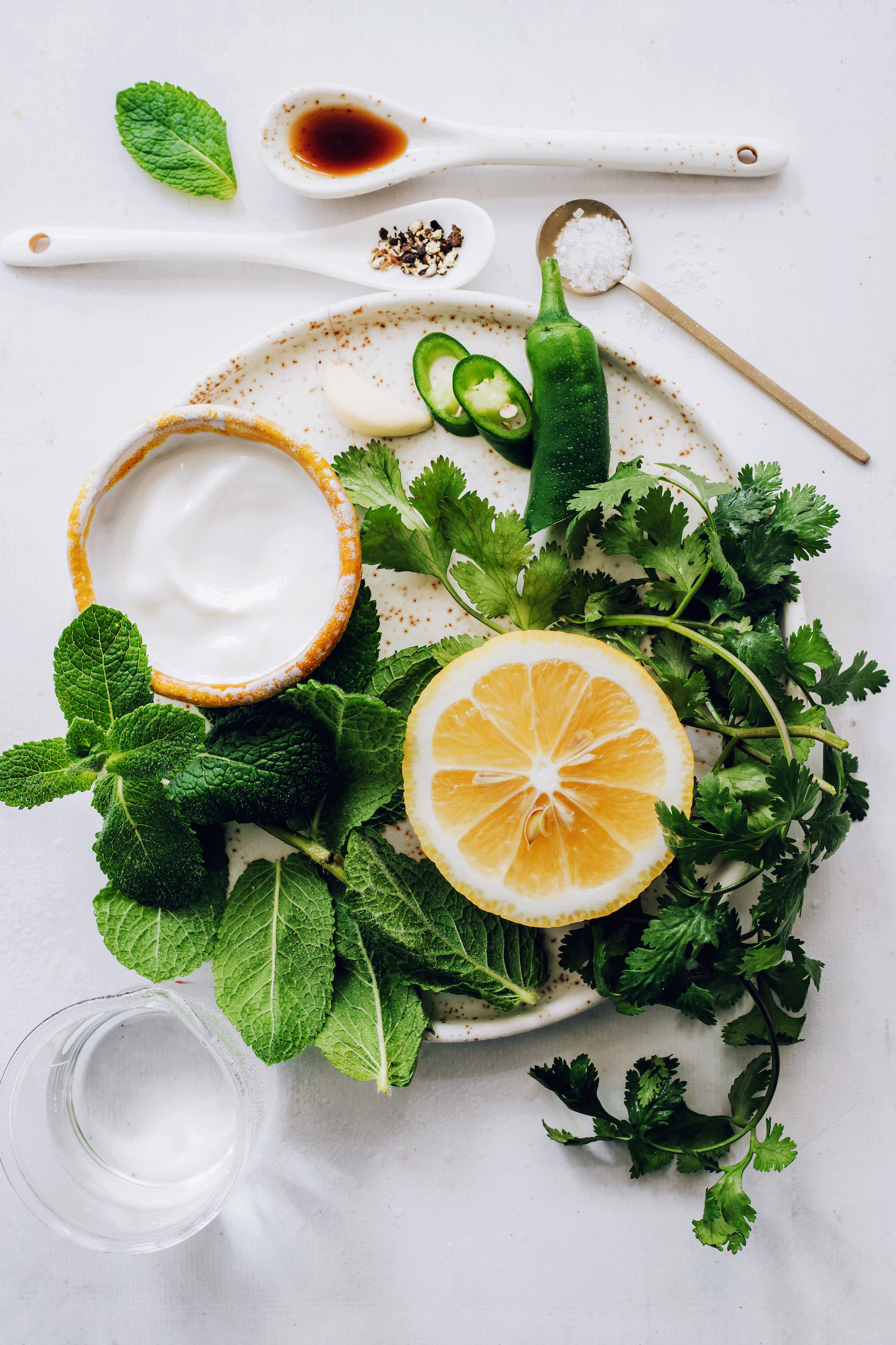 Maple syrup, salt, pepper, and water around a plate with coconut yogurt, mint, cilantro, lemon, jalapeno, and garlic