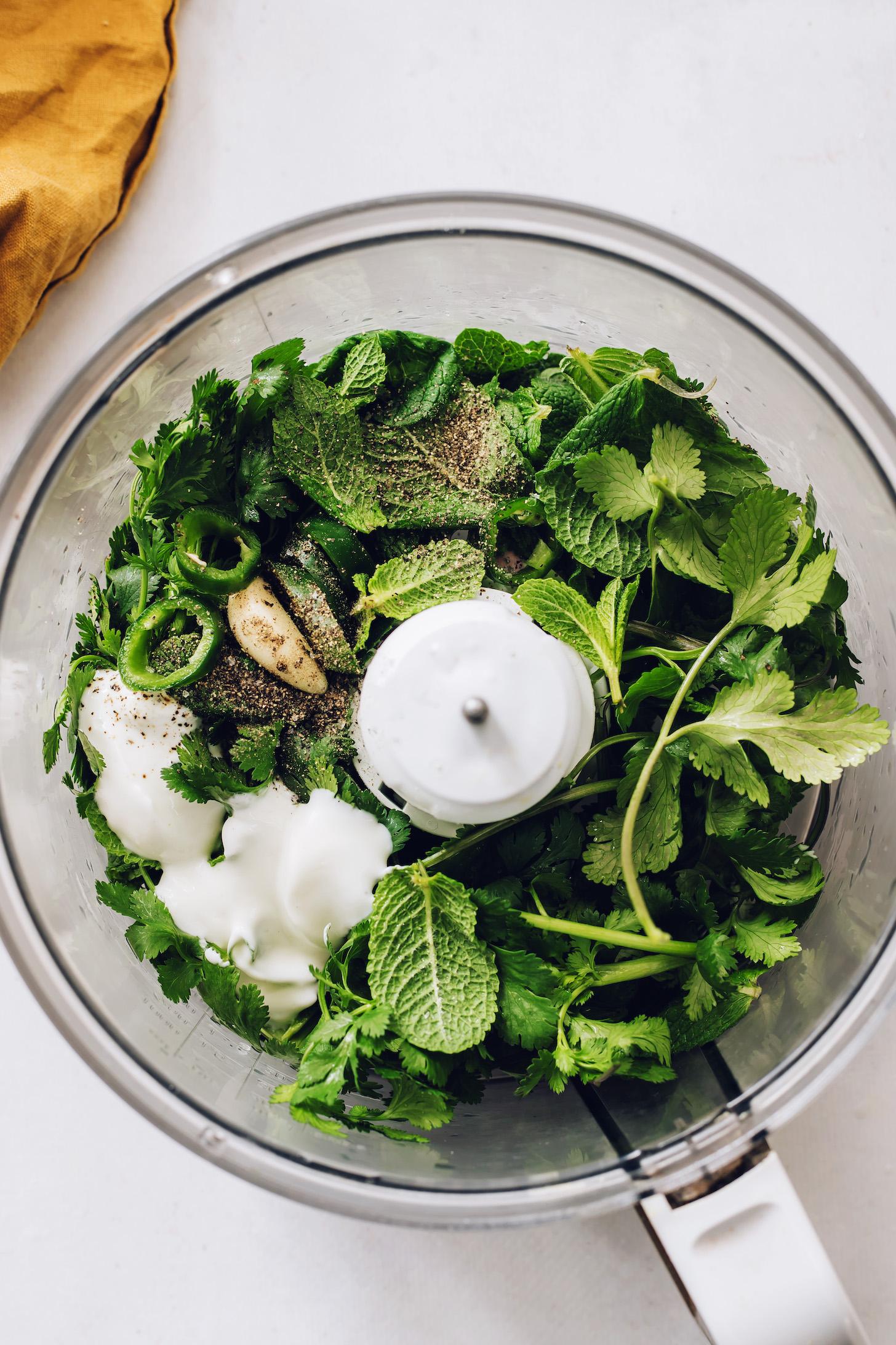 Food processor with mint leaves, cilantro, garlic, jalapeño, lemon juice, maple syrup, coconut yogurt, salt, and pepper