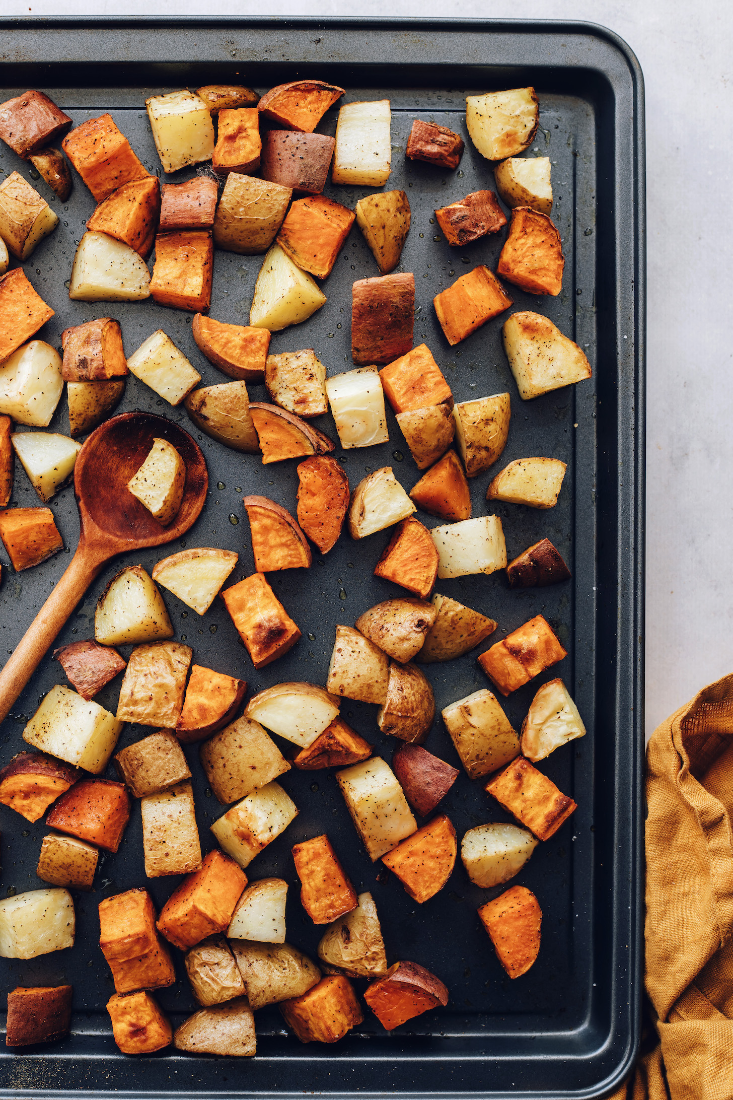 Wooden spoon on a baking sheet of roasted gold and sweet potatoes