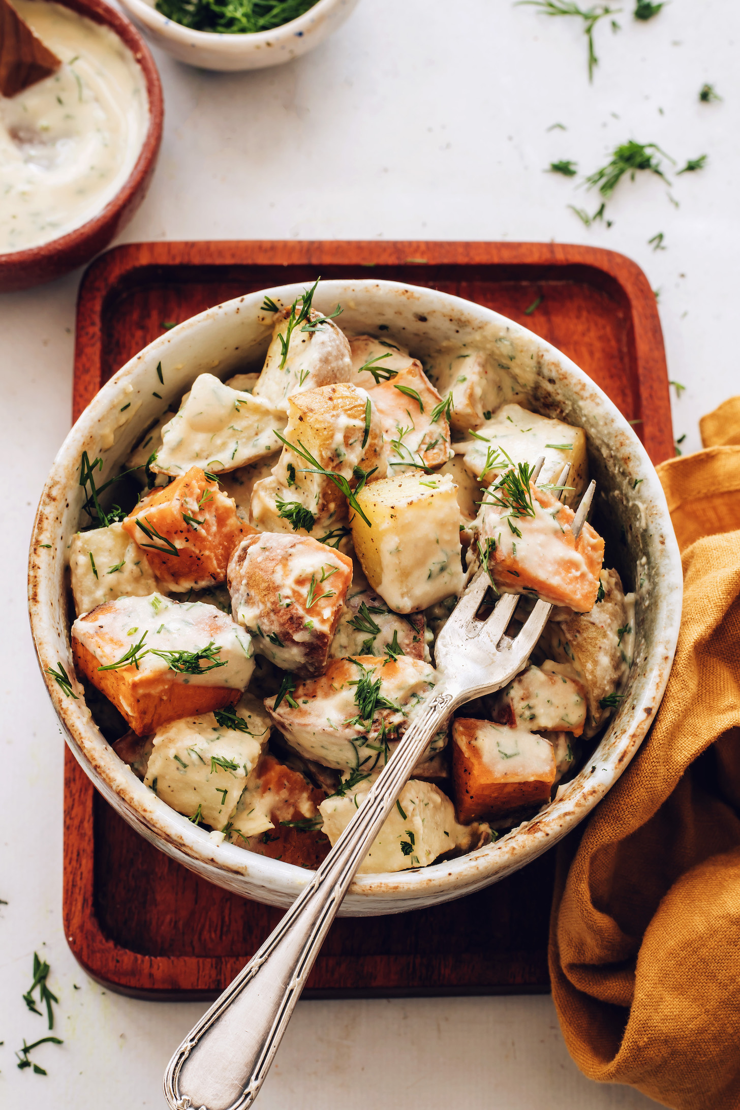 Fork in a bowl of roasted potato salad sprinkled with fresh dill