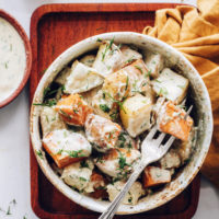 Fork in a bowl of roasted potato salad with garlic dill dressing