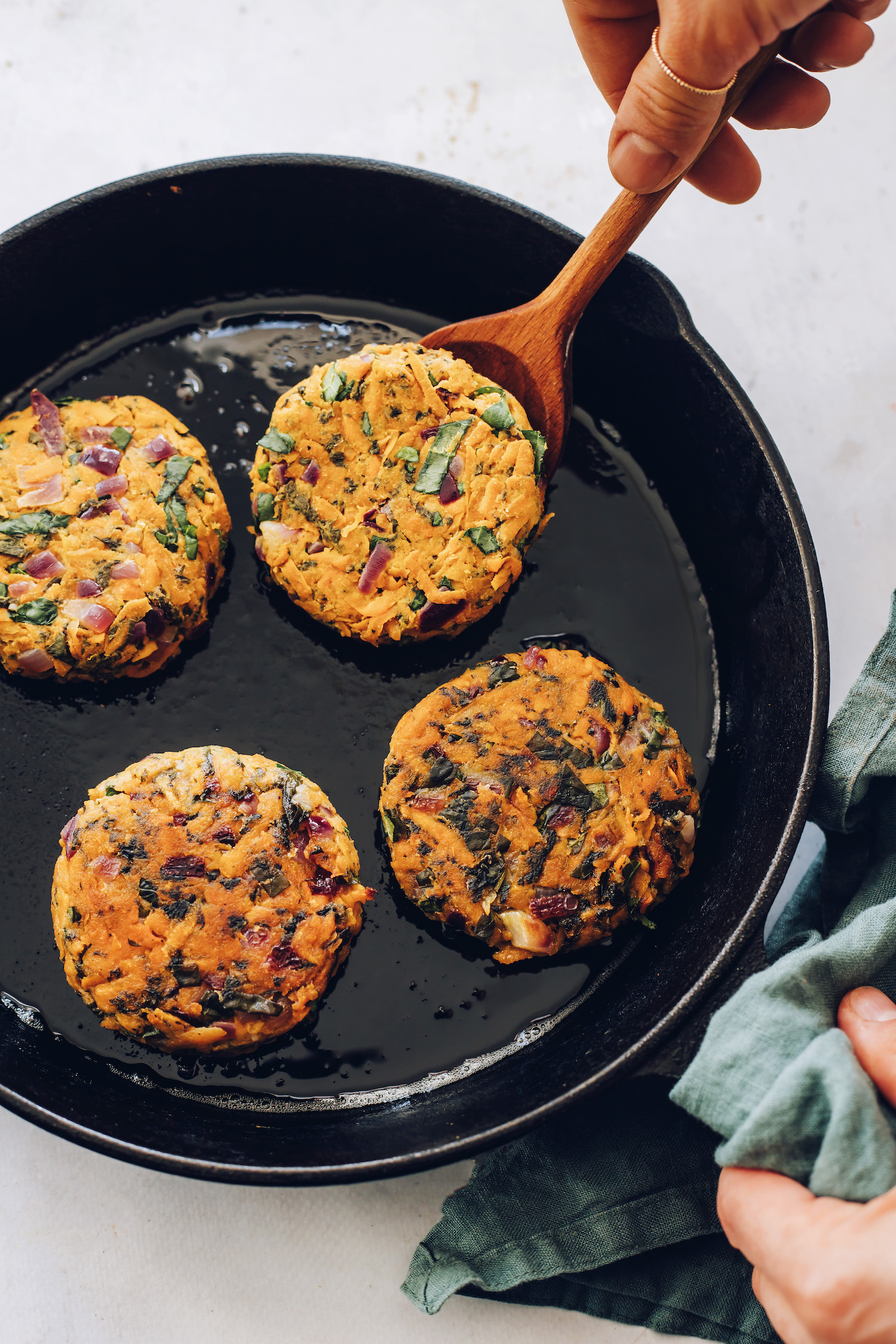 Partially cooked sweet potato fritters in a cast iron skillet