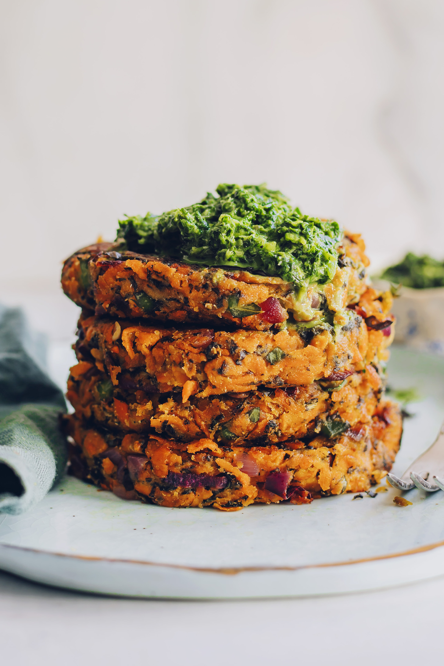 Stack of sweet potato fritters topped with mint chutney