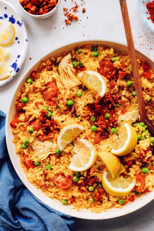 Pan of vegan paella topped with lemon wedges