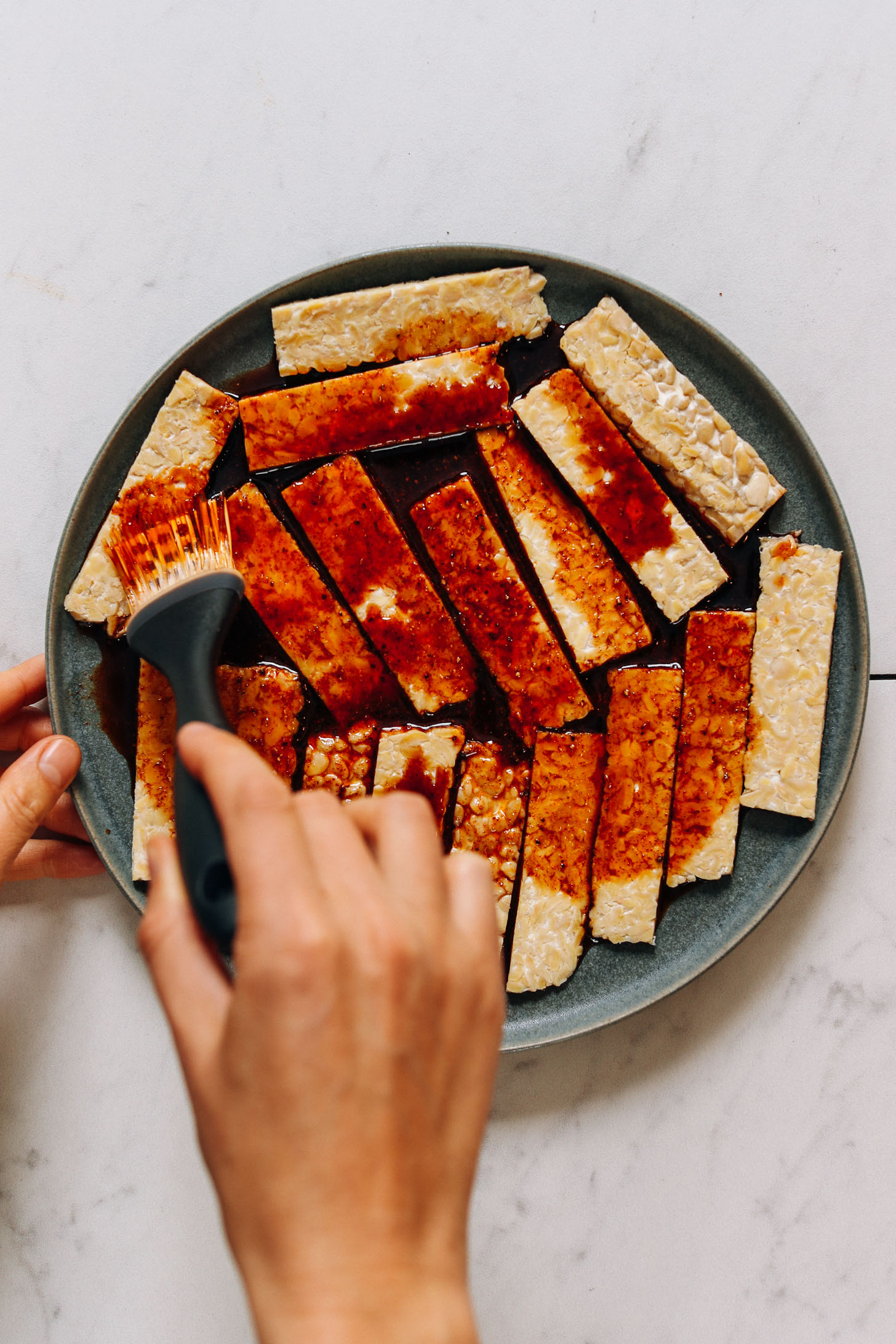 Using a pastry brush to spread marinade on tempeh bacon