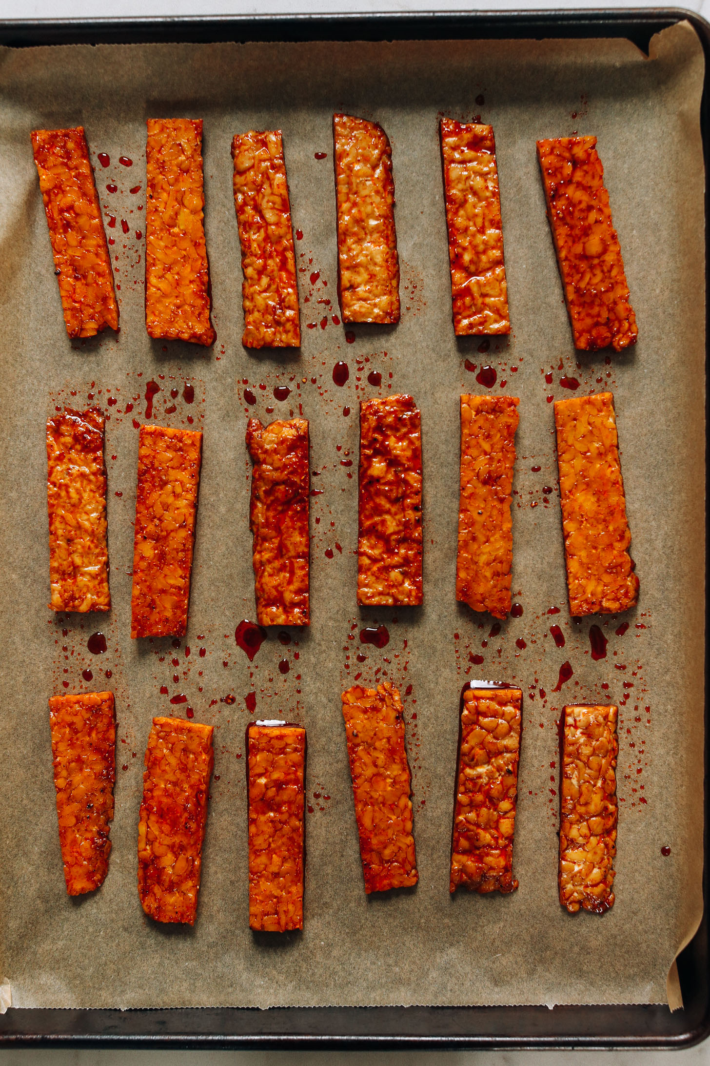 Baking sheet with thinly sliced strips of tempeh coated in a marinade