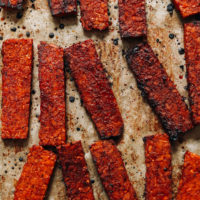 Strips of vegan tempeh bacon on a baking sheet