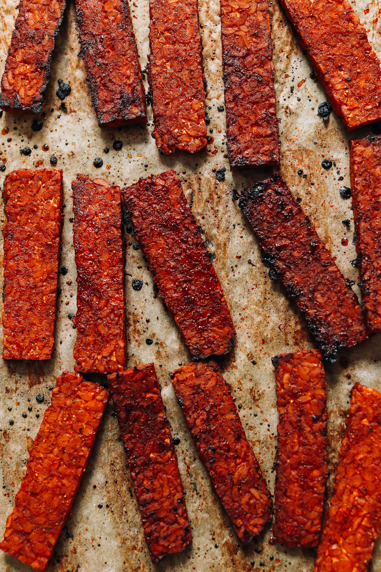 Baked tempeh bacon strips on a baking sheet