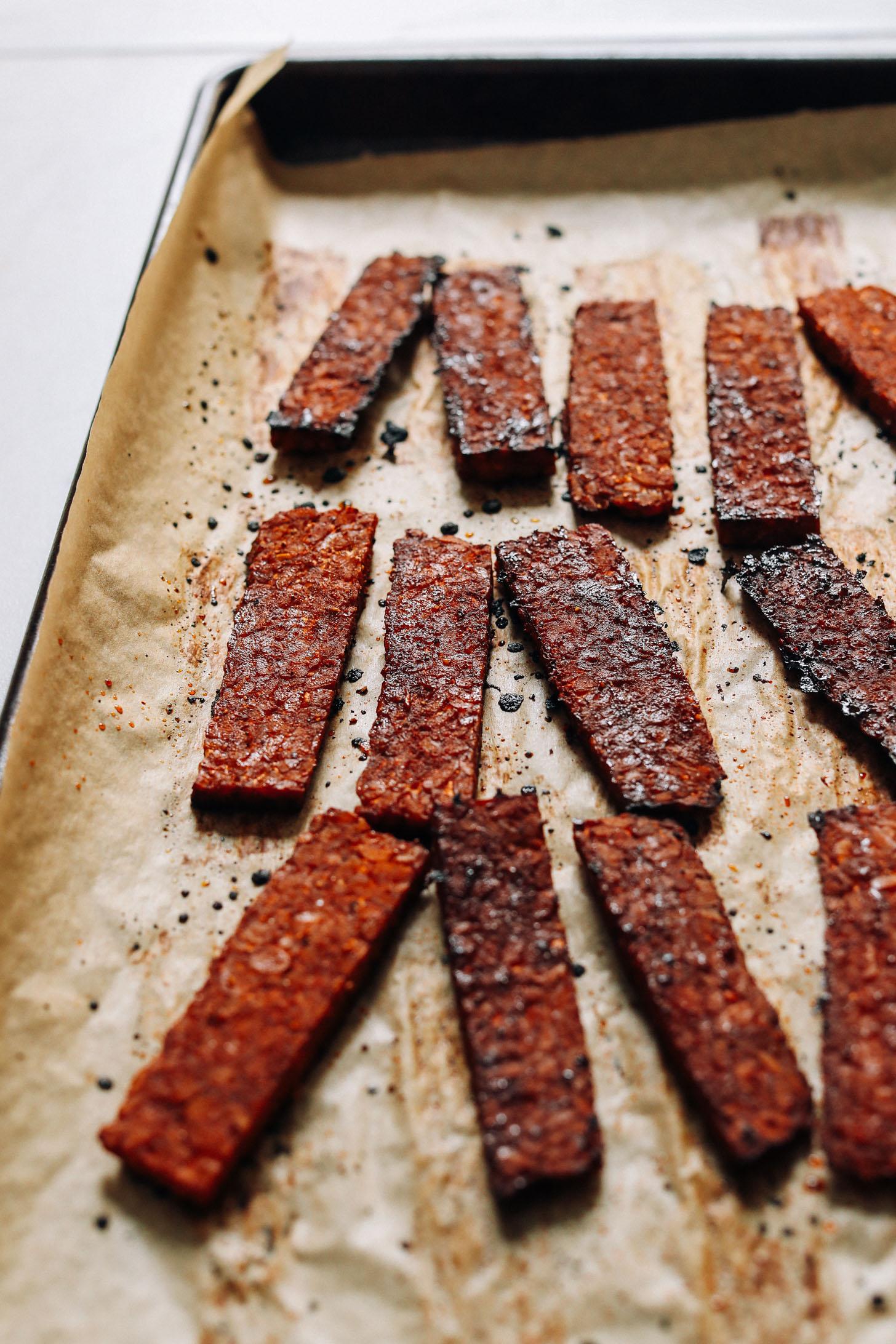 Strips of crispy tempeh bacon on a baking sheet