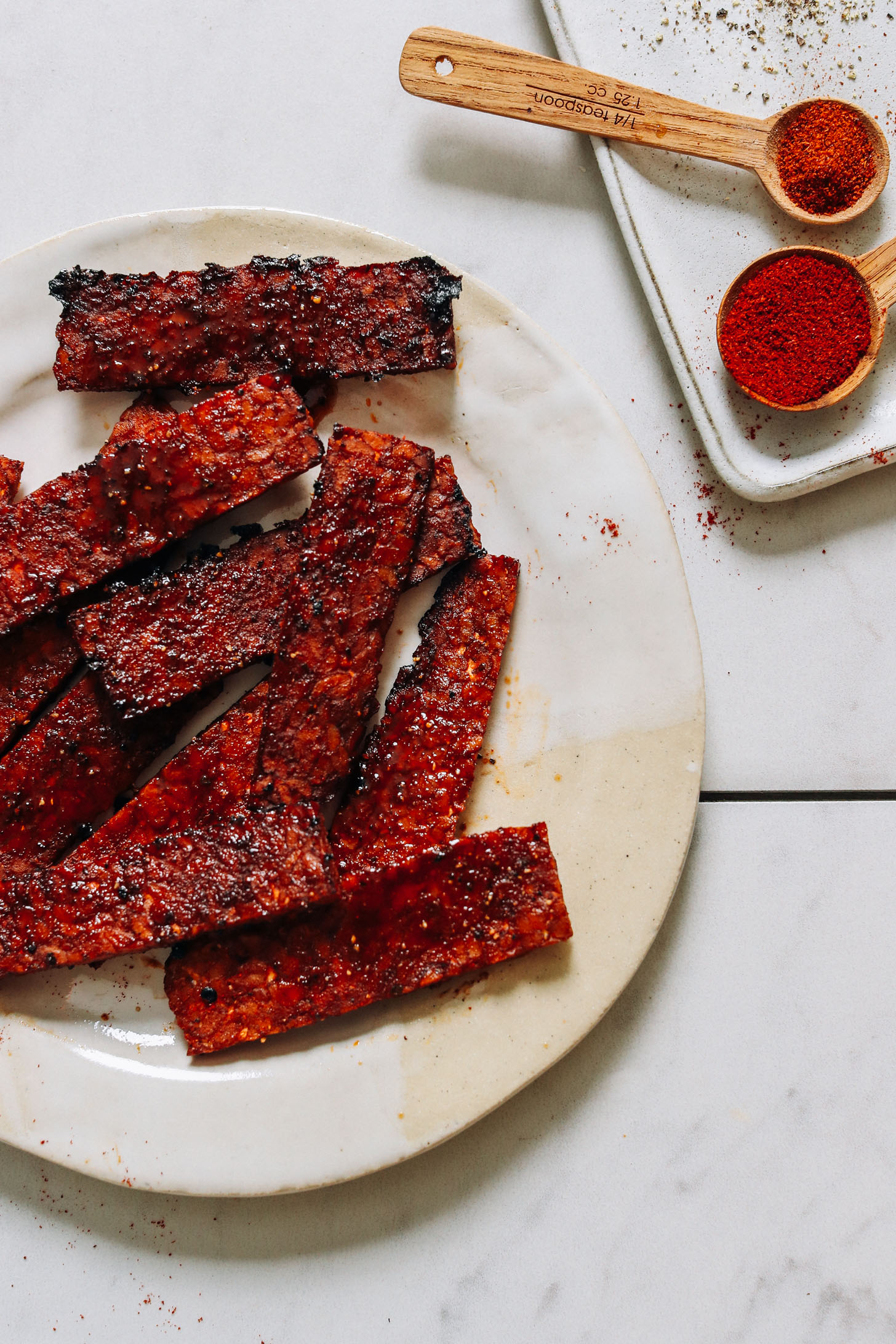 Spices next to a plate of vegan tempeh bacon slices
