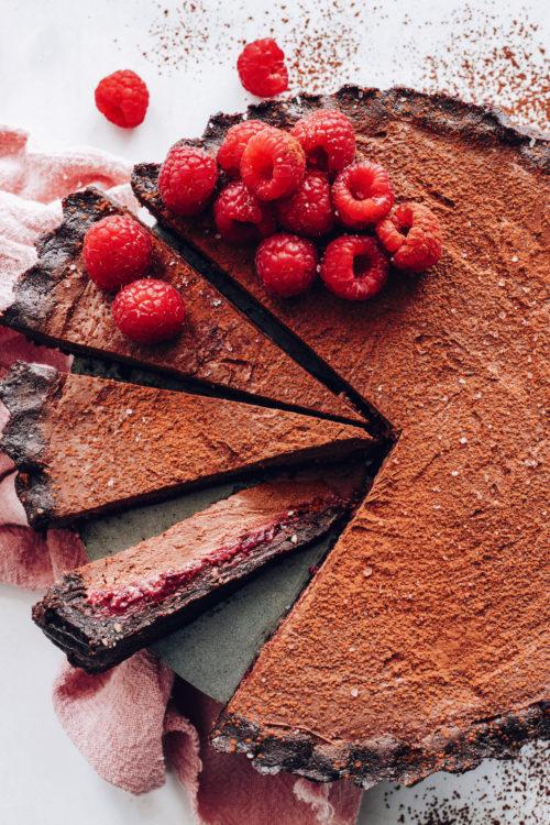 Partially sliced vegan chocolate ganache tart topped with fresh raspberries