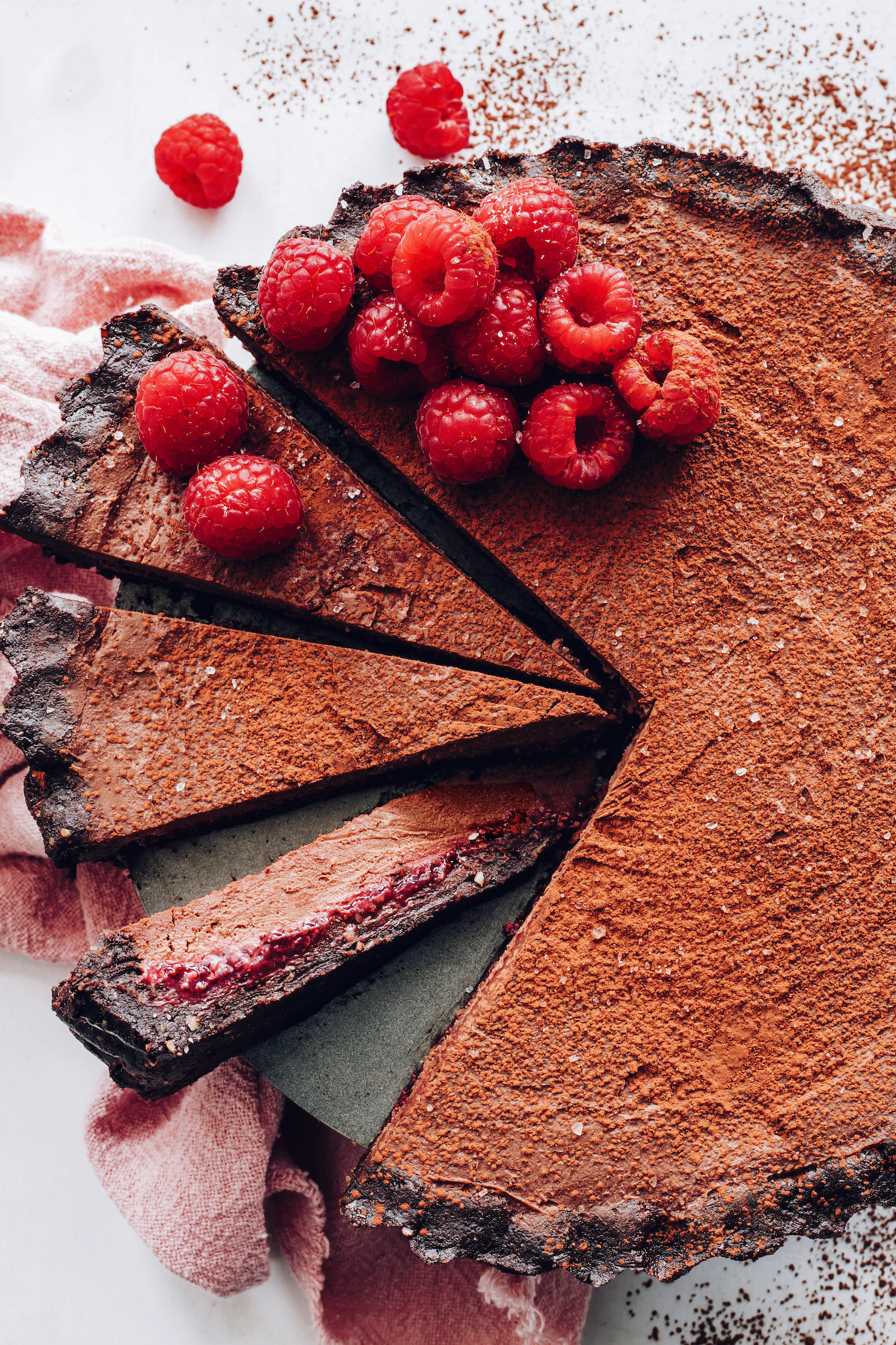 Vegan chocolate ganache tart topped with fresh raspberries and a dusting of cocoa powder