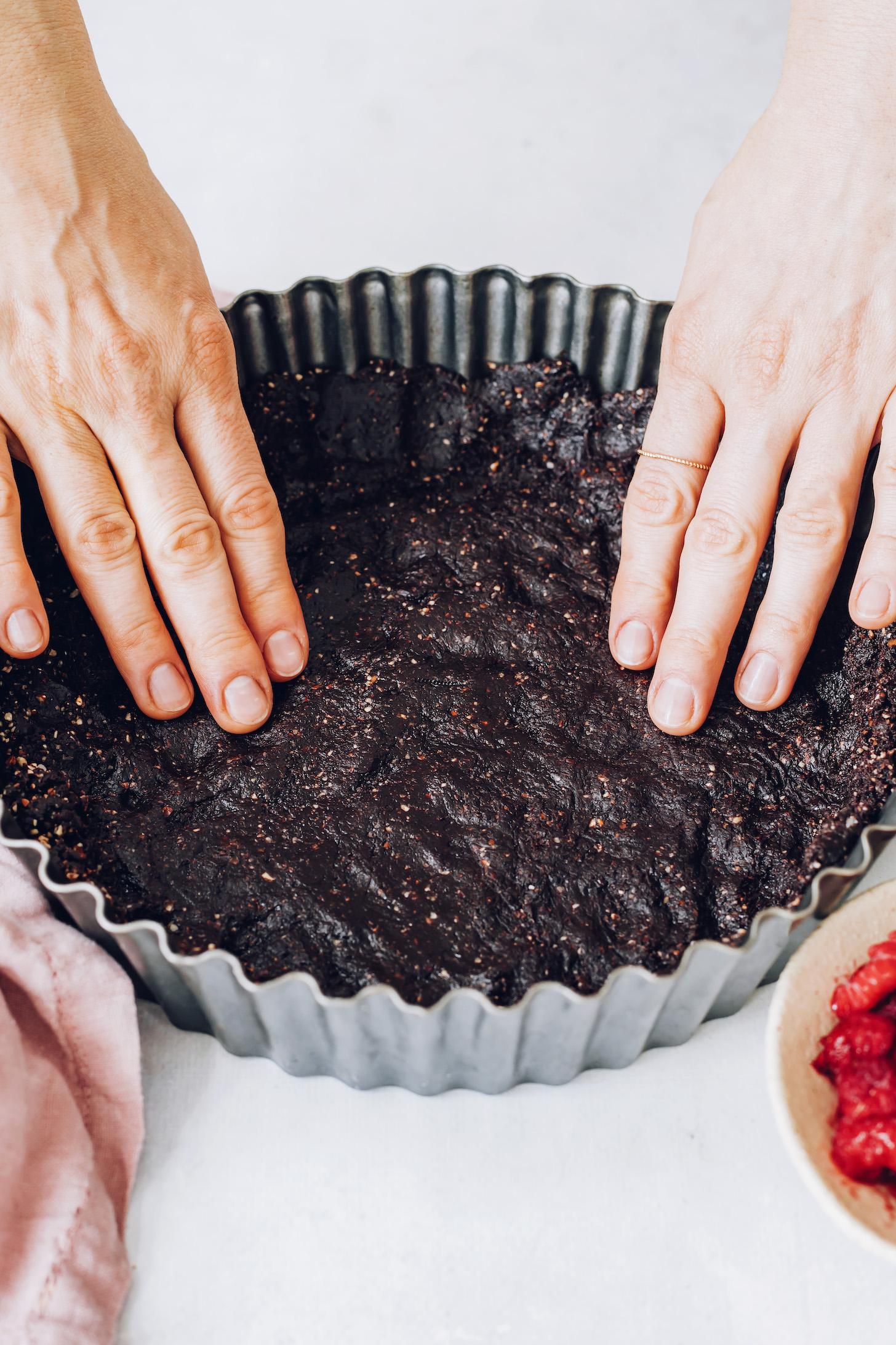 Pressing the dark chocolate date crust into a tart pan