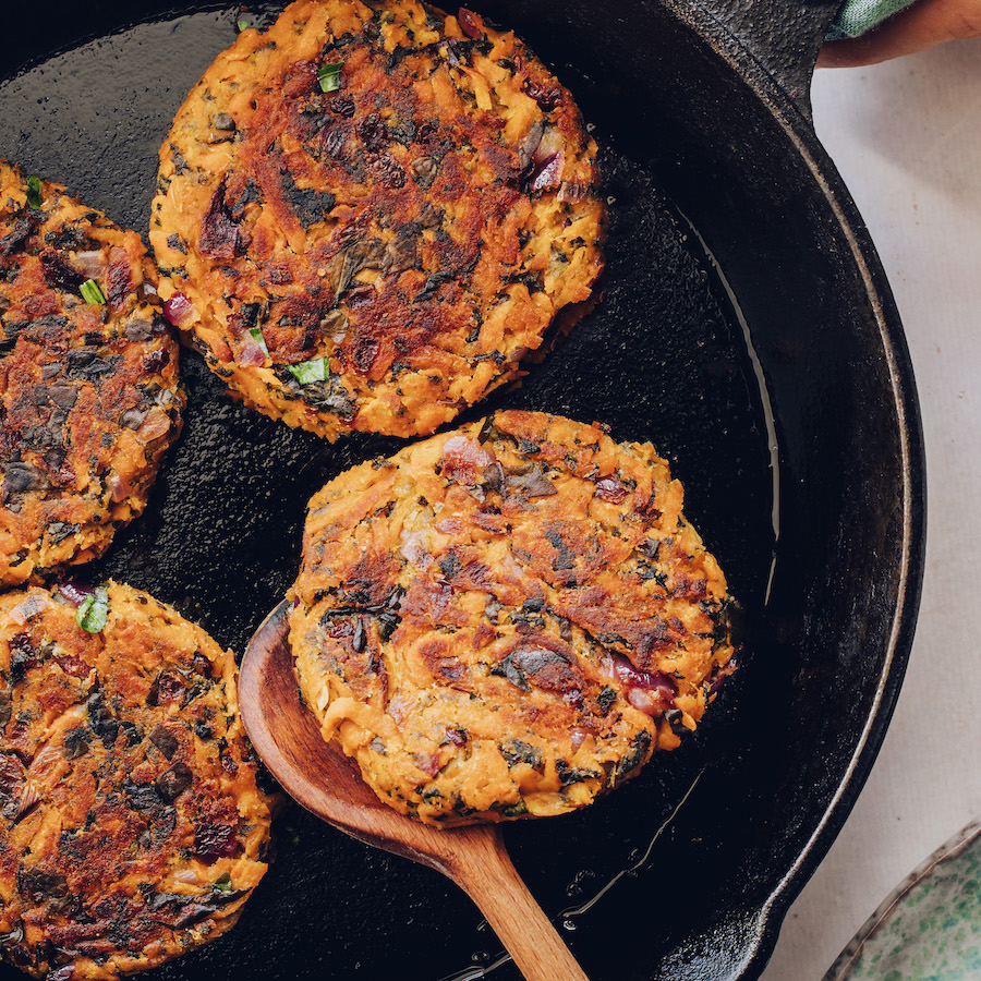 Flipping a sweet potato fritter in a skillet