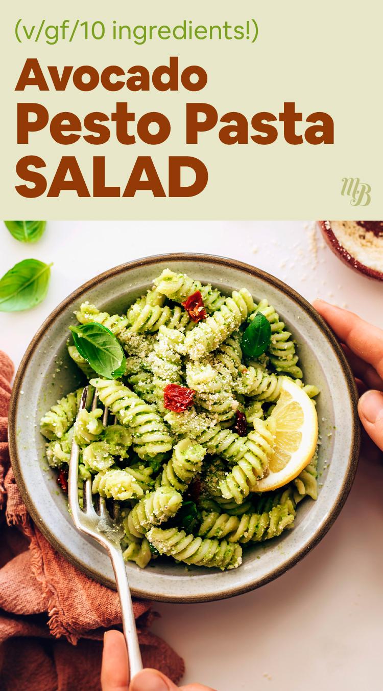 Руки держат миску веганского и безглютенового салата с песто из авокадо, свежего базилика, вяленых на солнце помидоров и лимона.