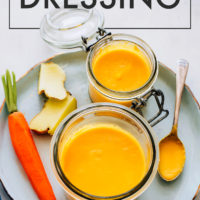 Jar of vegan & gluten-free carrot ginger dressing with fresh carrots and ginger