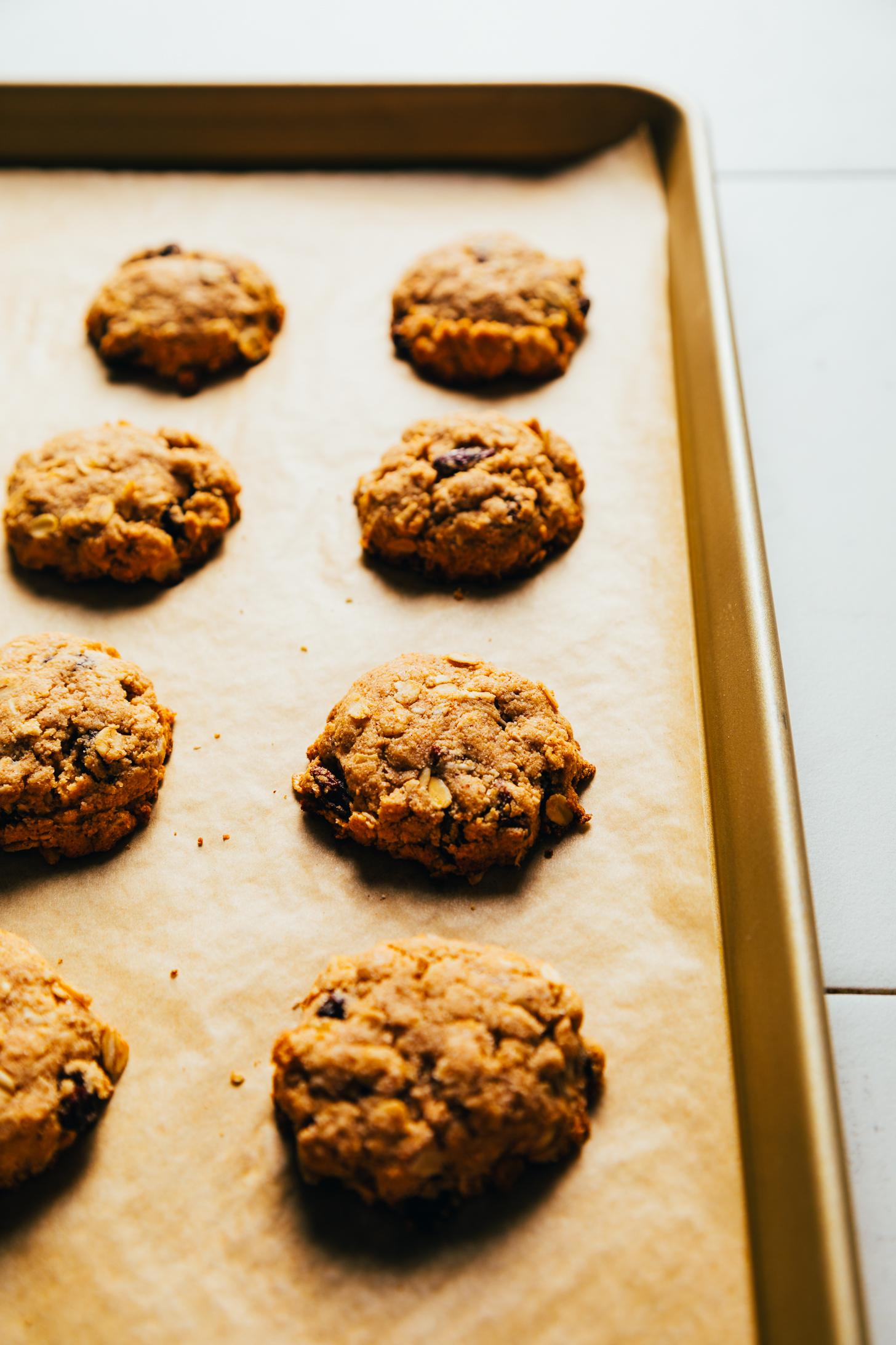 Parchment-lined baking sheet of vegan oatmeal raisin cookies